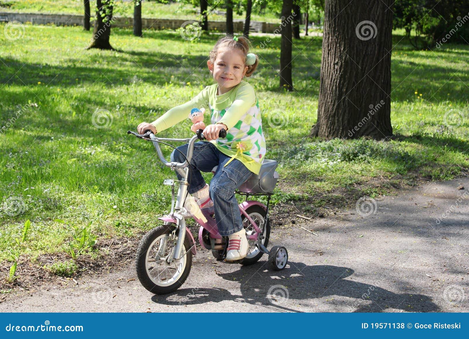 Niña Montando Su Bicicleta En Un Parque: Bicicleta Del Montar A Caballo De La Chica Joven Fotos De