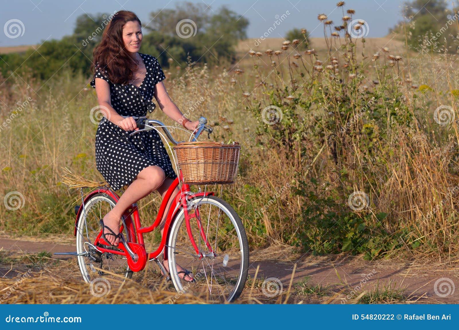 Bicicleta del vintage del montar a caballo de la mujer joven
