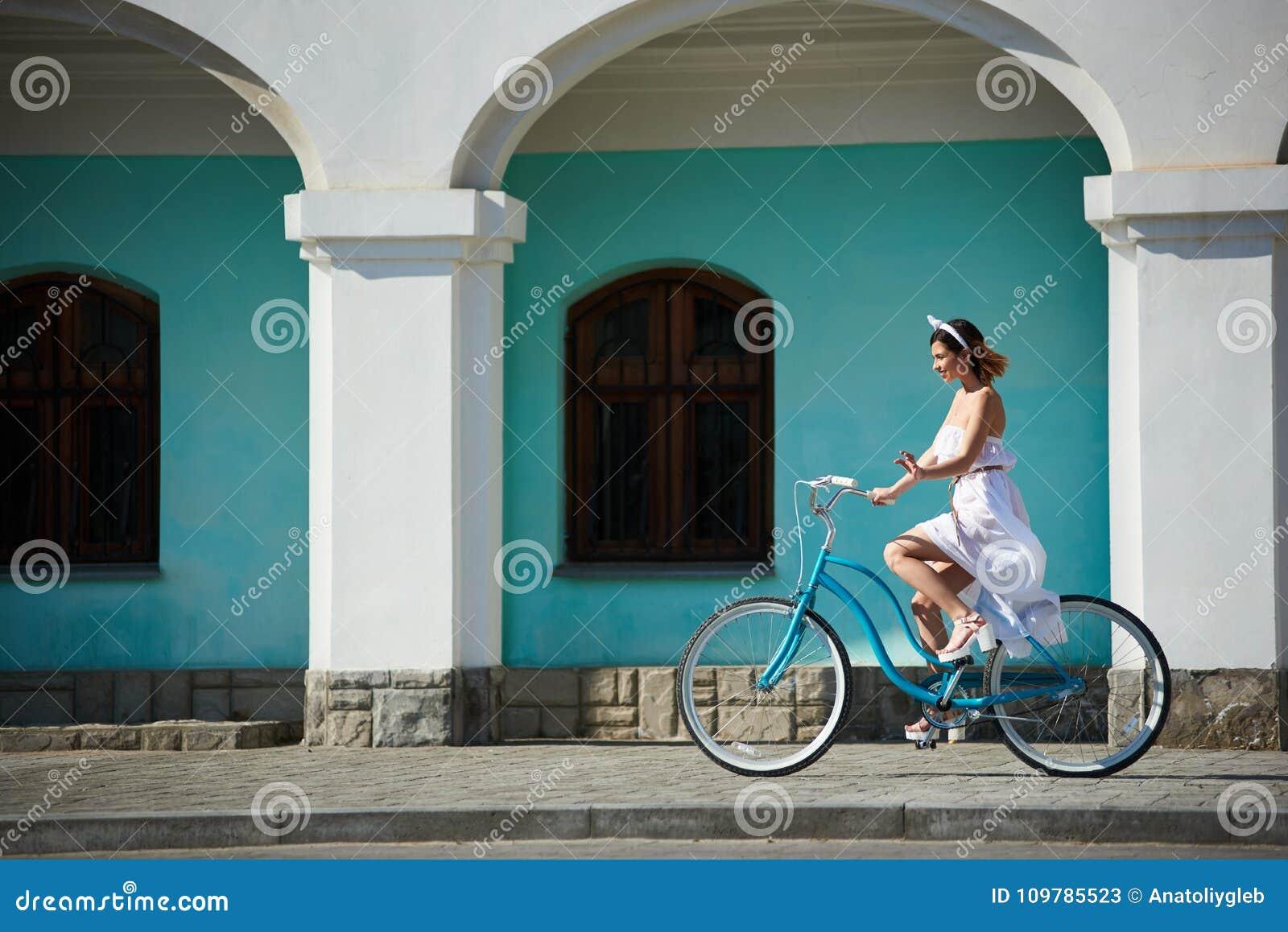 Bicicleta feliz bonita da equitação da mulher na cidade