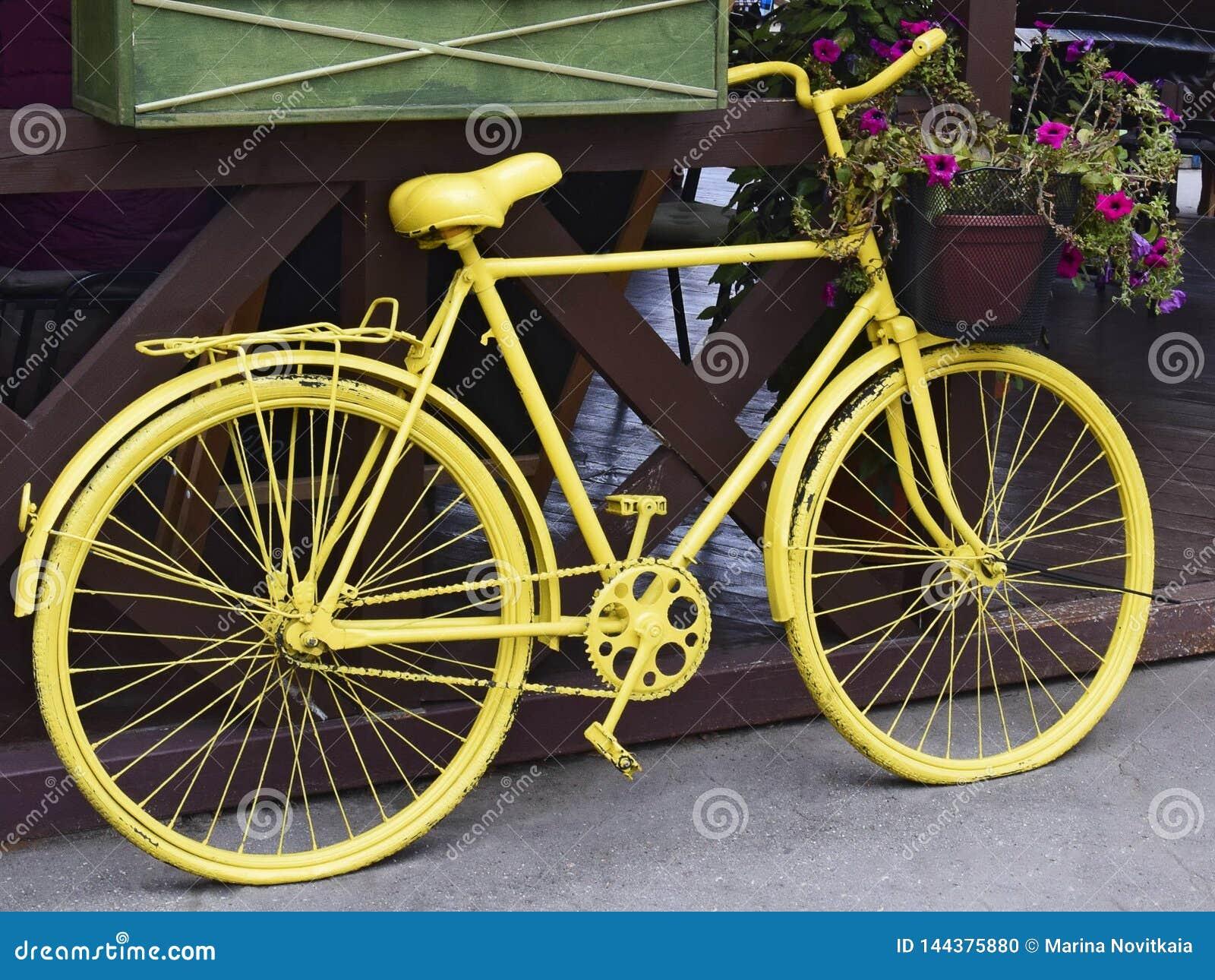 Bicicleta retra amarilla con una cesta de flores
