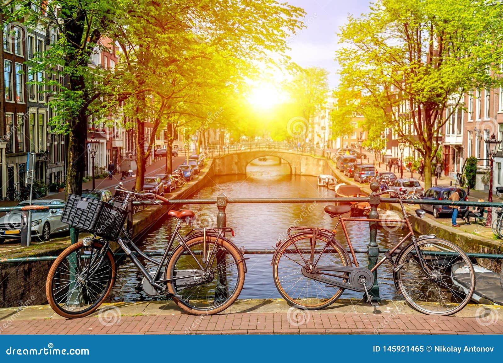 Bicicleta vieja en el puente en Amsterdam, Pa?ses Bajos contra un canal durante d?a soleado del verano Opini?n ic?nica de la post