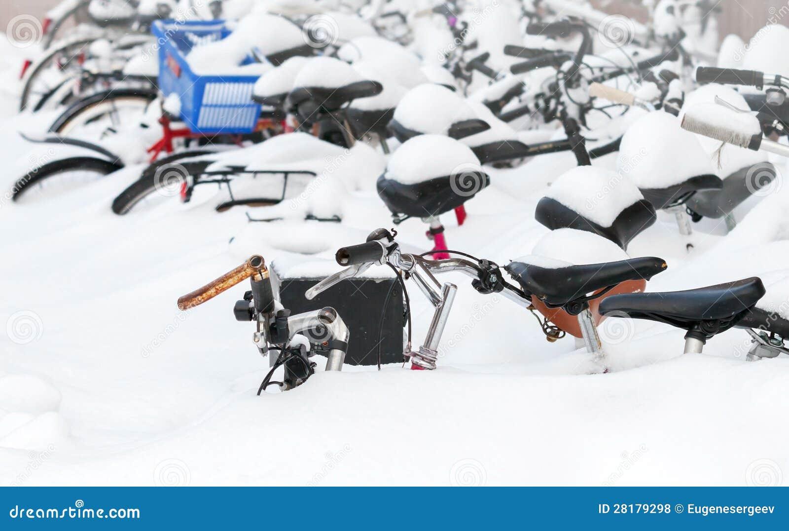 Bicicletas cobertas com a neve no snowdrift grande