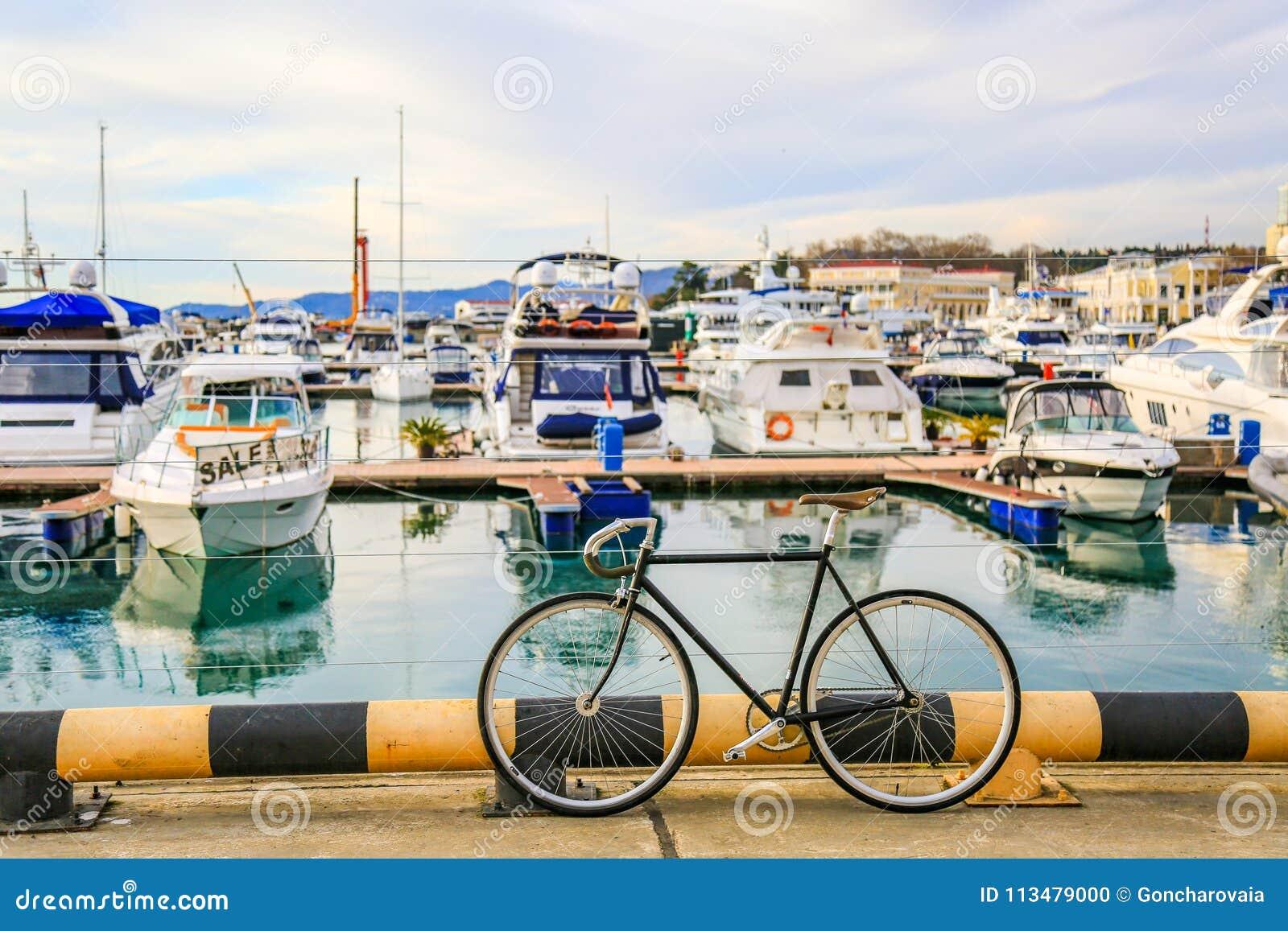 Bicicletas estacionadas no cais Os barcos de motor e os iate luxuosos entraram no porto marítimo Rua da cidade e água azul Férias