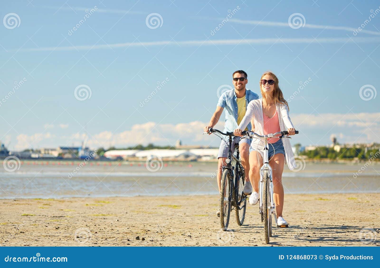 Bicicletas jovenes felices del montar a caballo de los pares en la playa