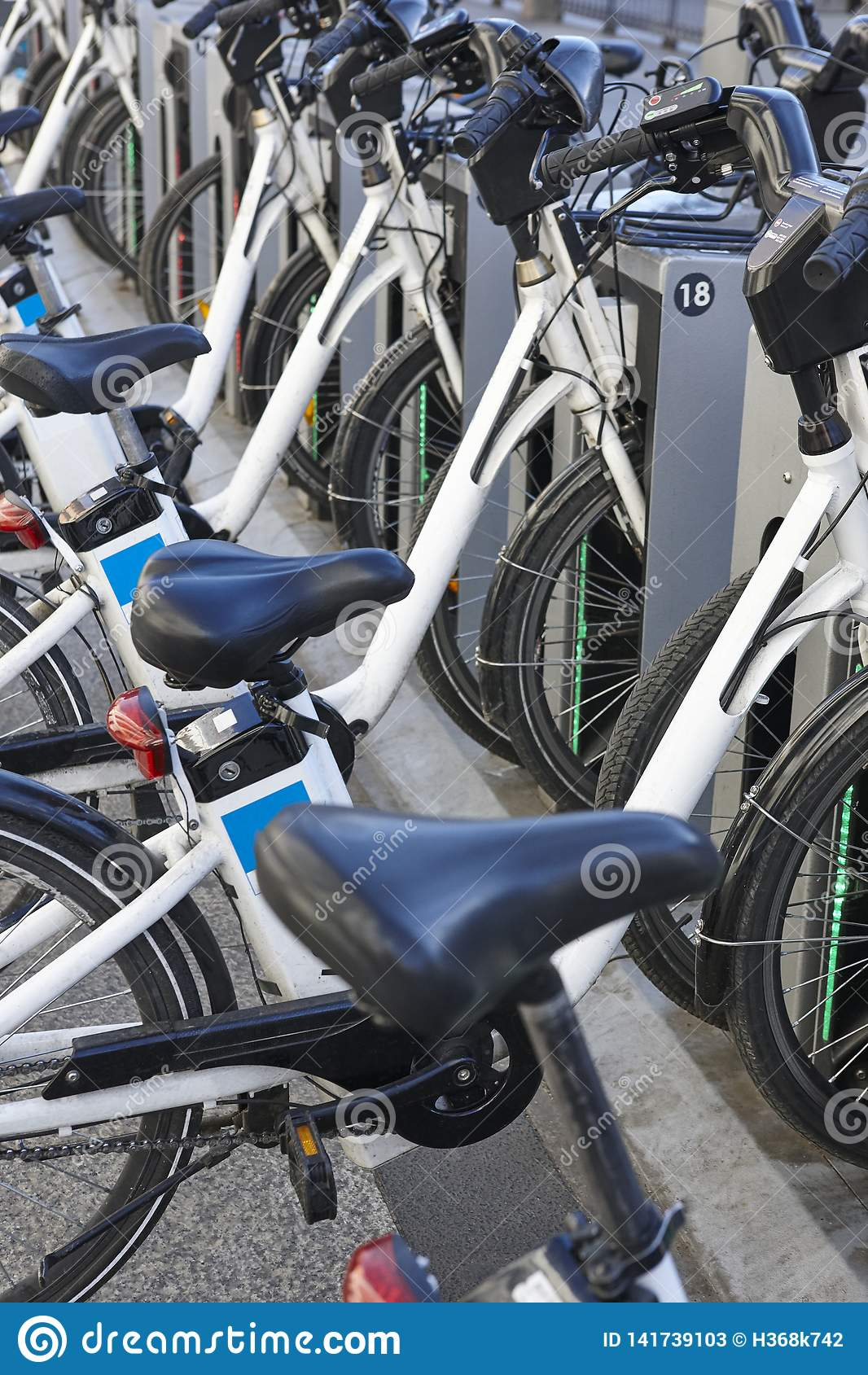 Bicicletas urbanas de carregamento da bateria elétrica na cidade Mobilidade sustentável