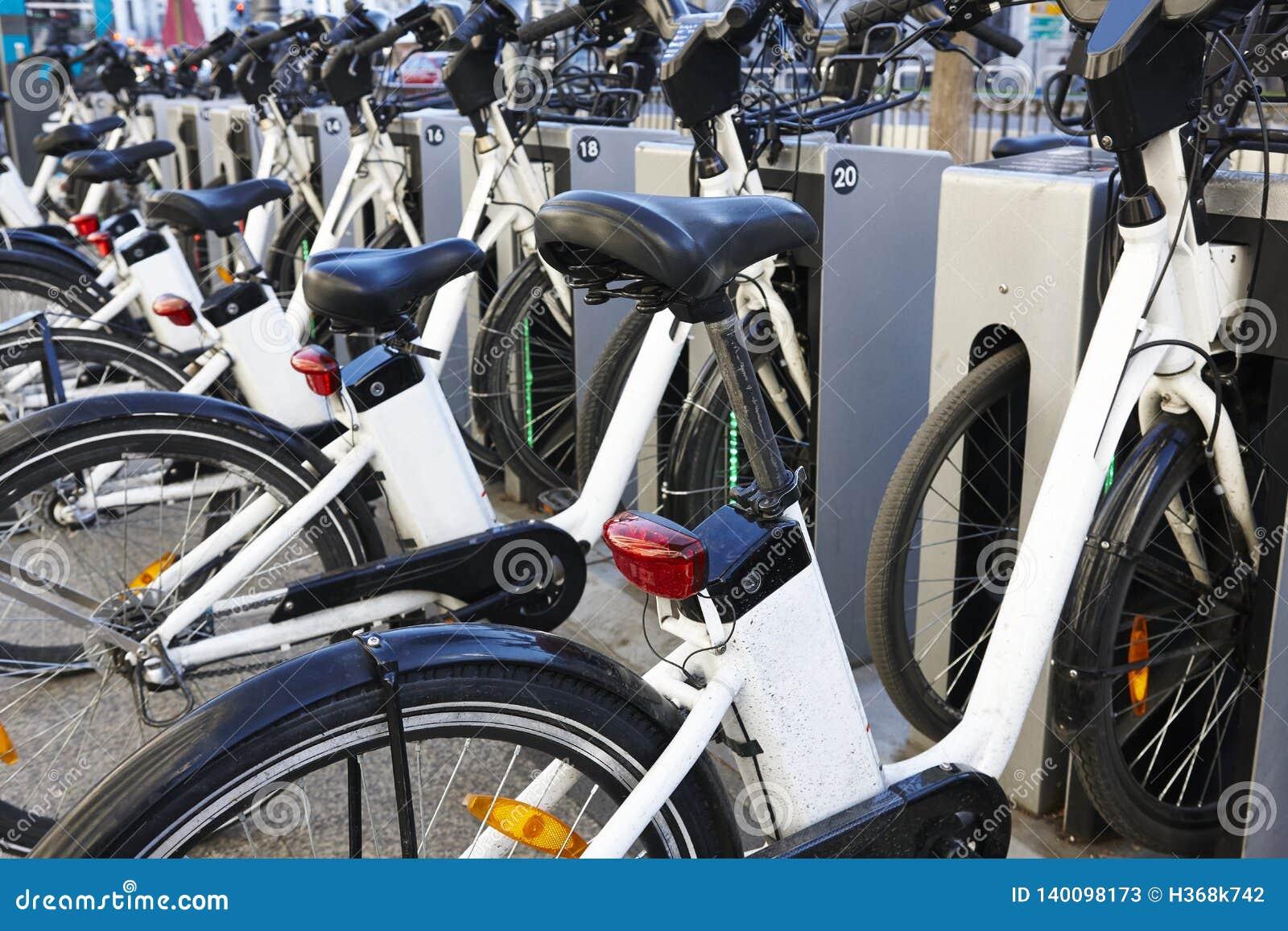 Bicicletas urbanas de carregamento da bateria elétrica na cidade mobilidade