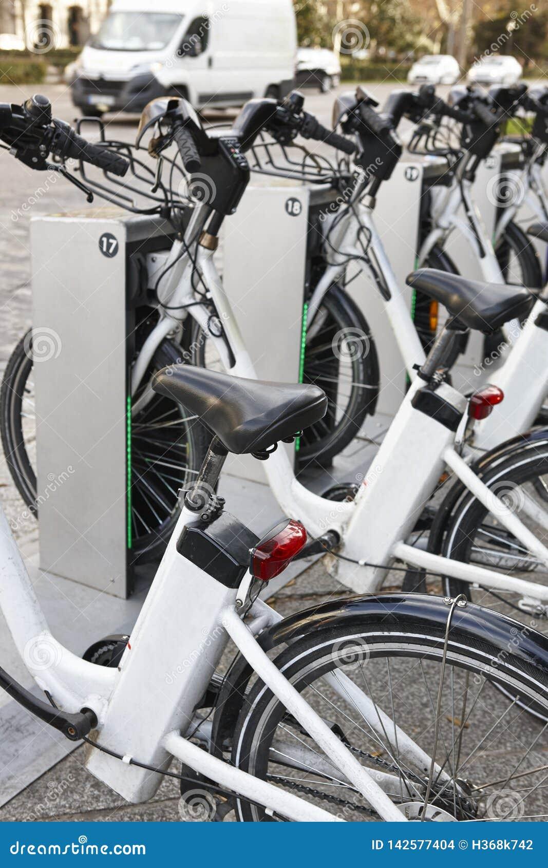 Bicicletas urbanas de carregamento da bateria elétrica na cidade Transporte de Eco