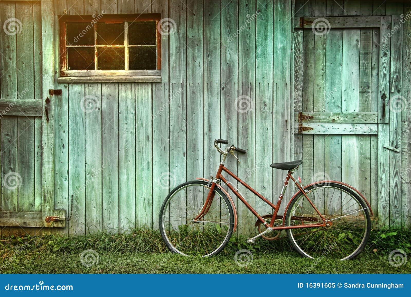 Bicicletta che si appoggia contro il granaio grungy