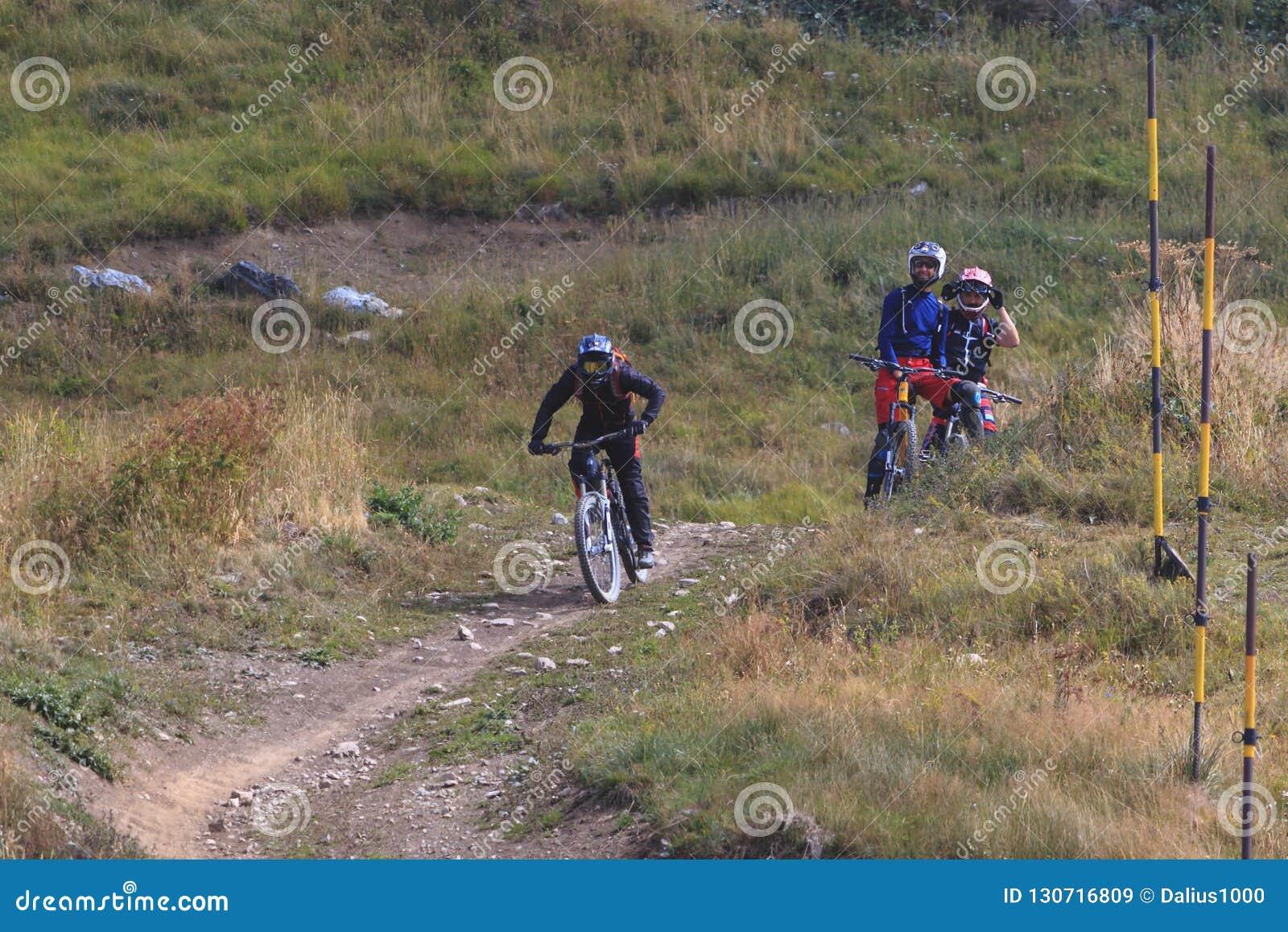 Bicicletta della montagna di guida dell uomo in discesa e due amici che lo guardano