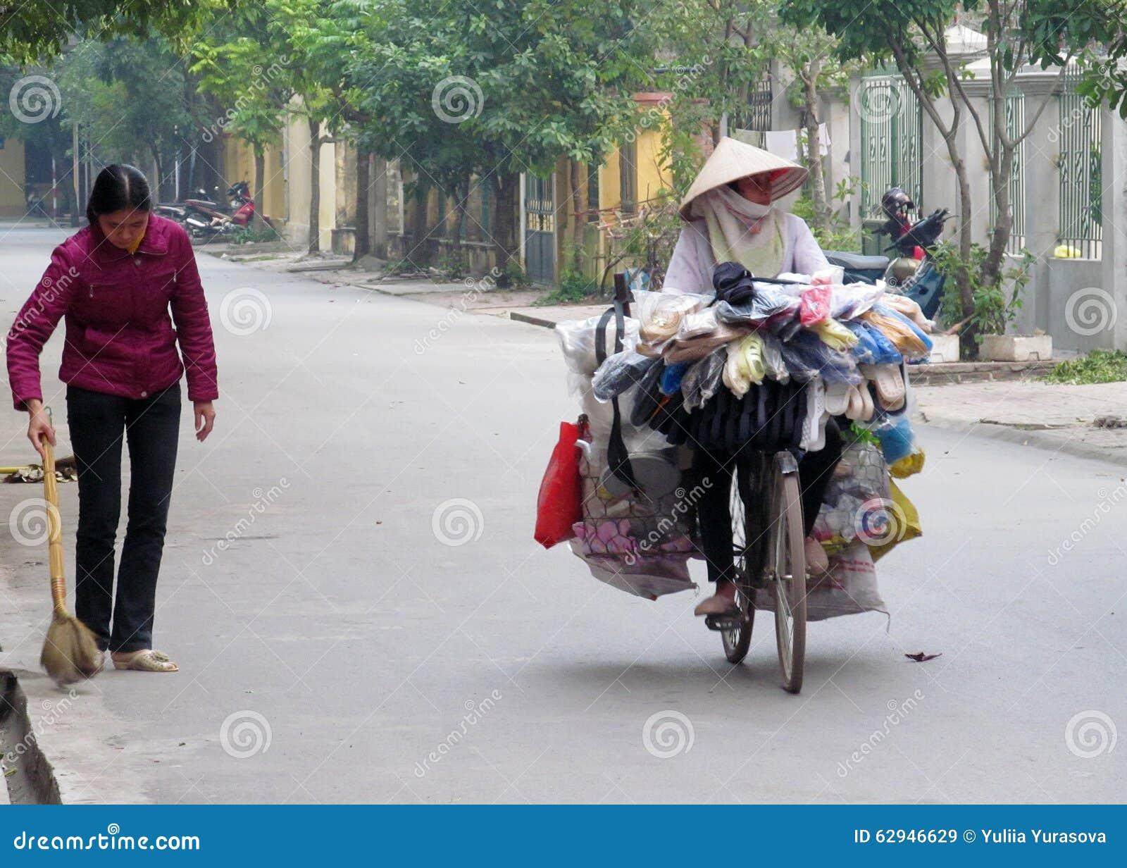 Bicicletta di guida della donna del Vietnam Donna asiatica che porta i cappelli  tradizionali fatti di paglia o di foglie di palma Cappello conico asiatico  ... d7844dcf5fa8