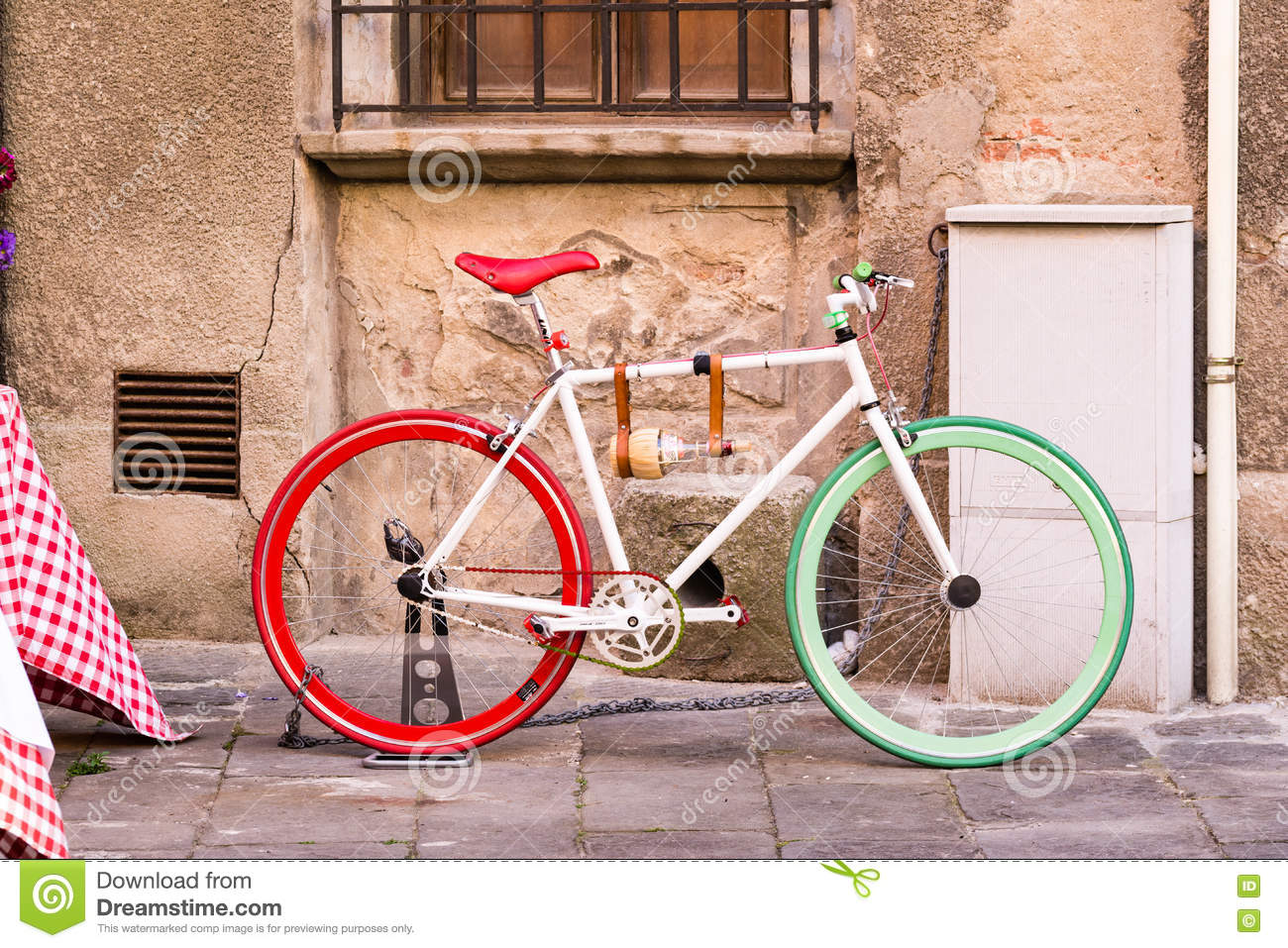 A bicycle with the colors of the Italian flag next to a wall in