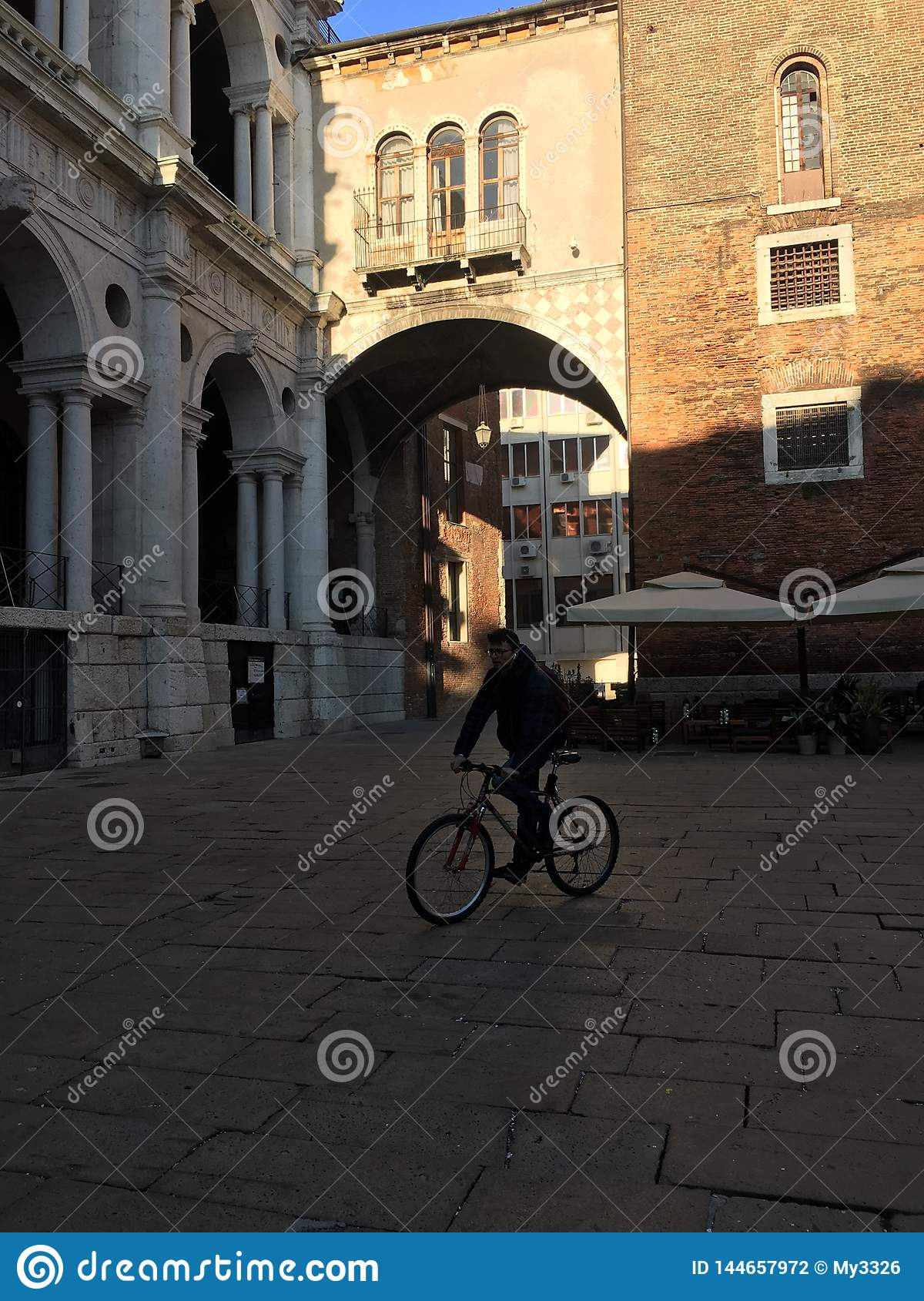 Bicycle man under a bridge in Rome