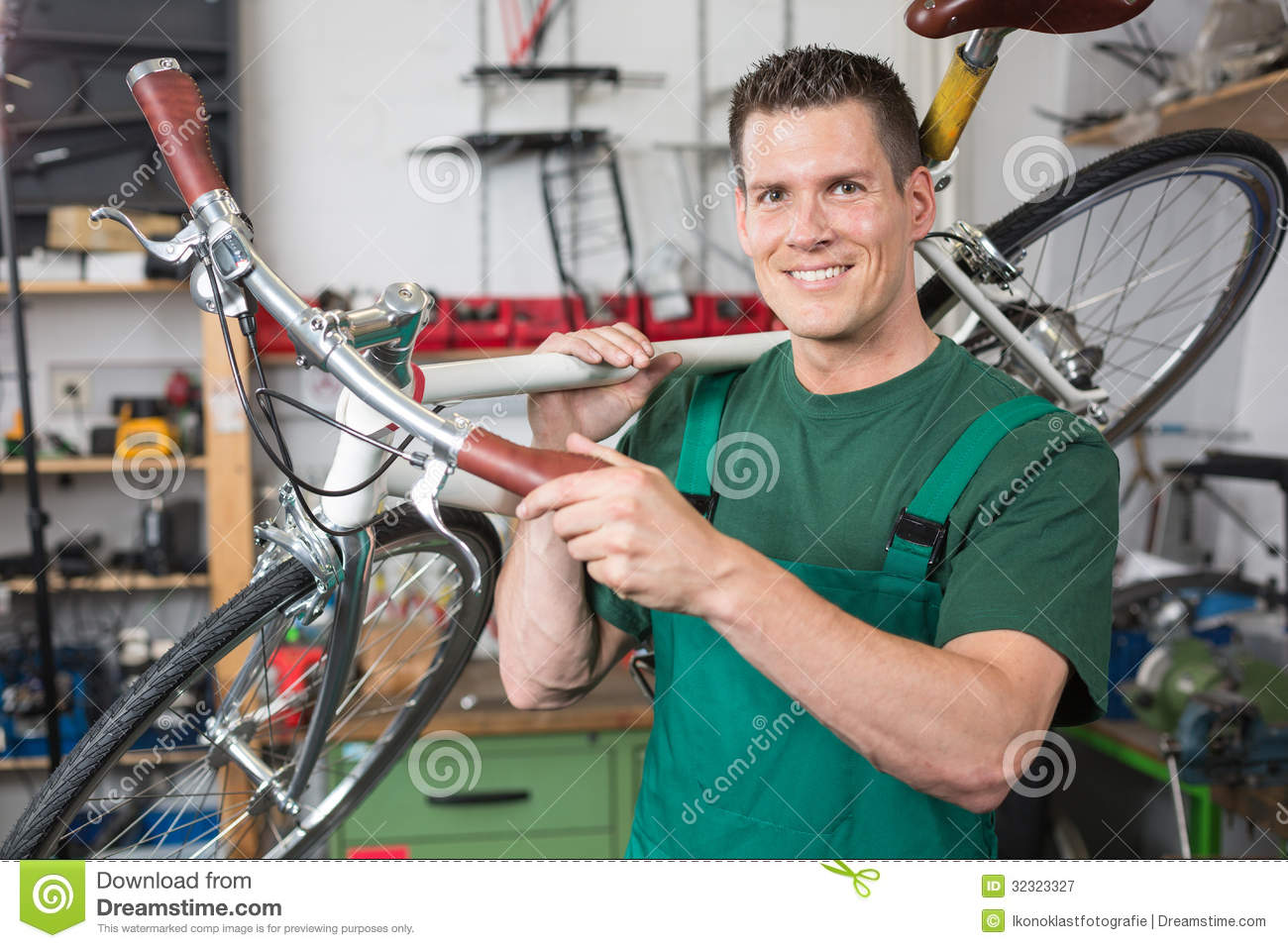 Bicycle mechanic carrying a bike in workshop smiling