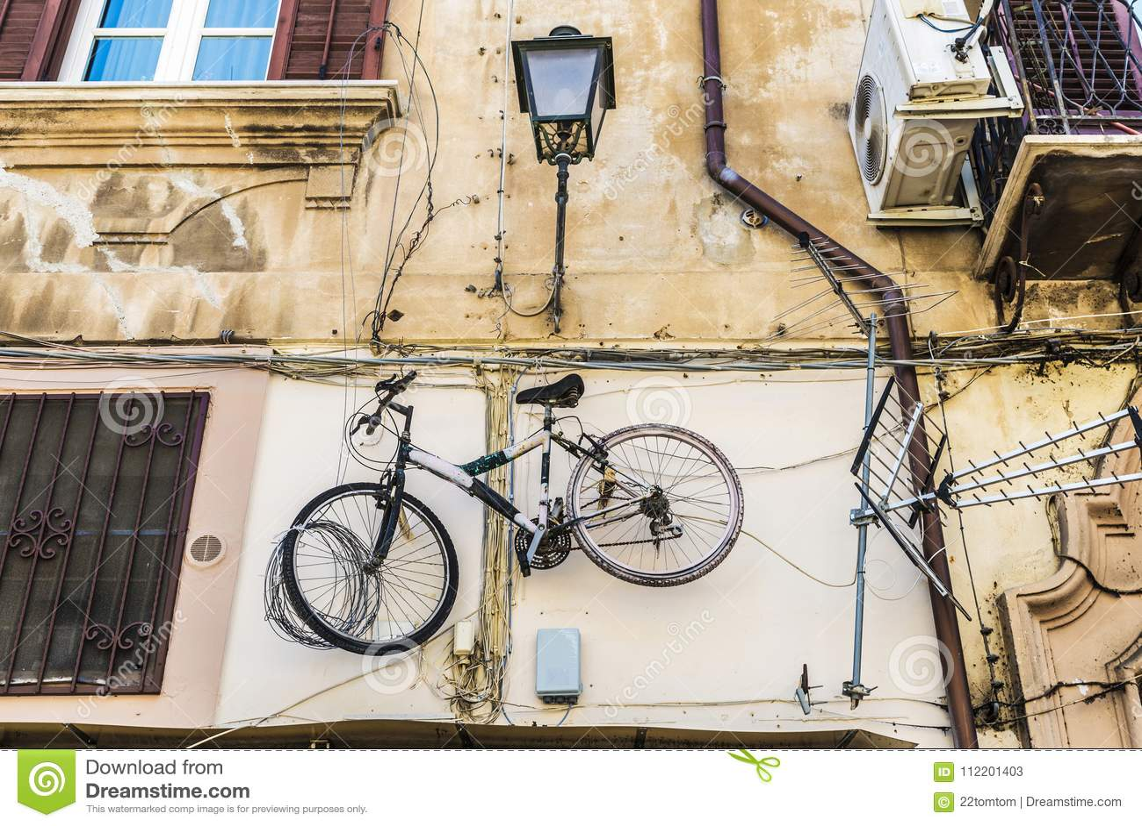 Bicycle a suspensão em uma parede velha em Palermo, Sicília, Itália