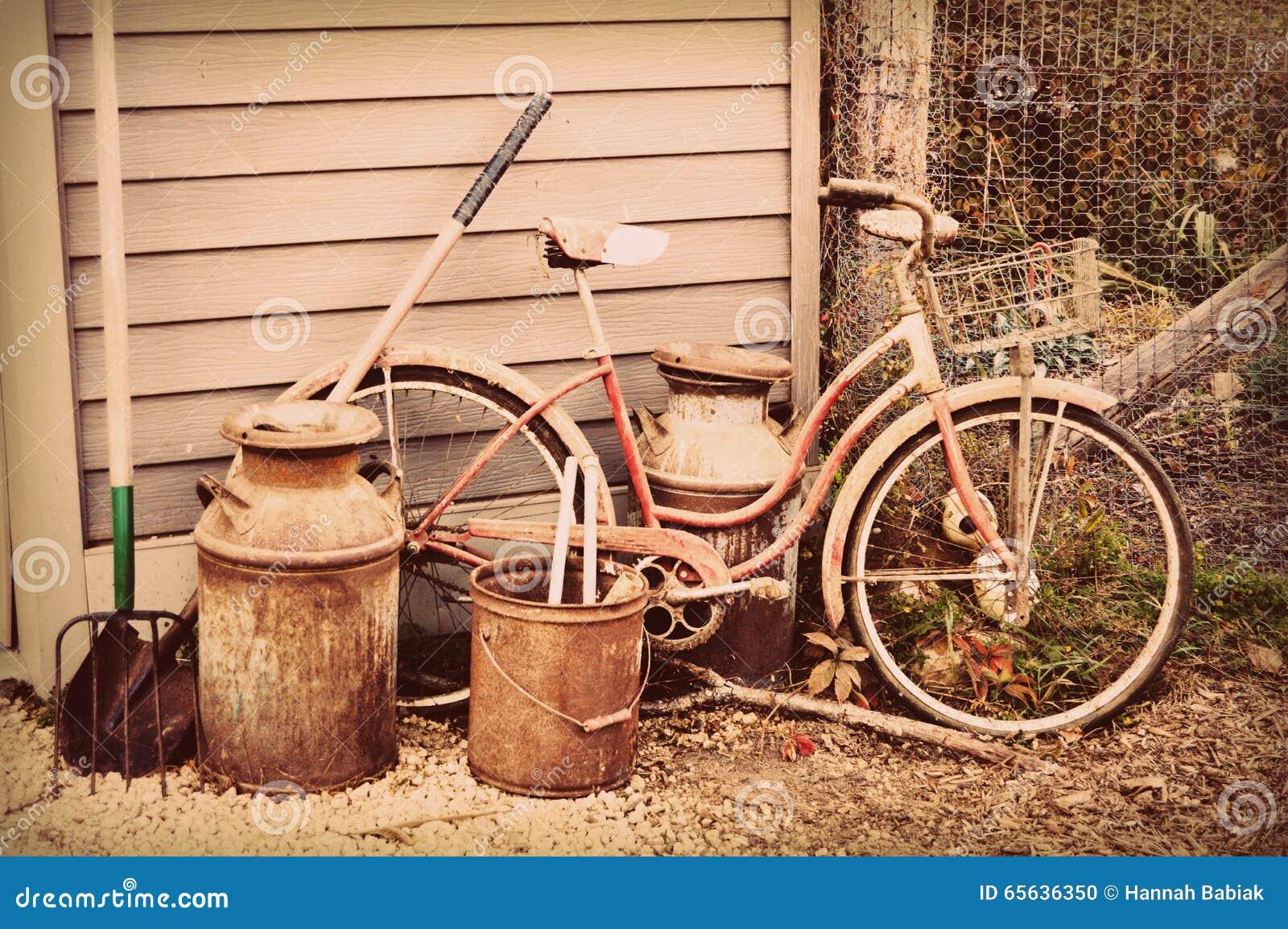Bicyclette, cruche de lait et outils antiques