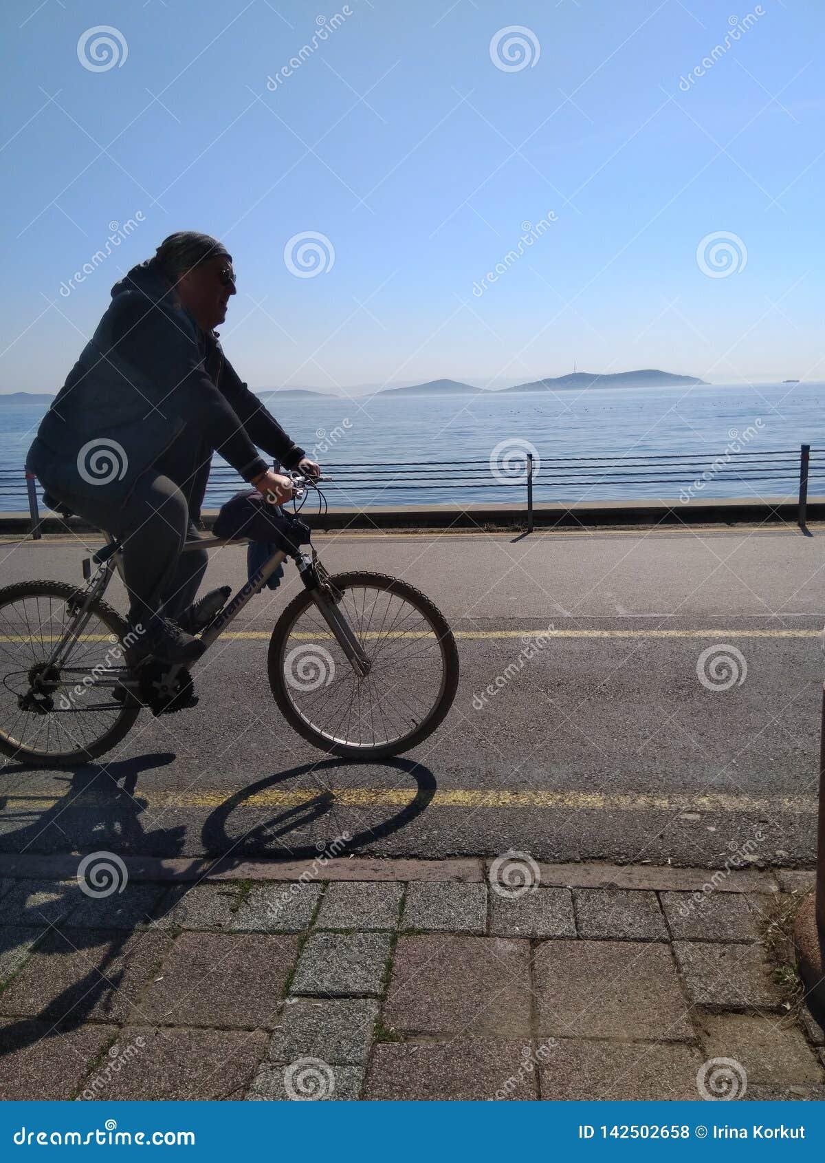 Bicyclette d équitation d homme près de la mer