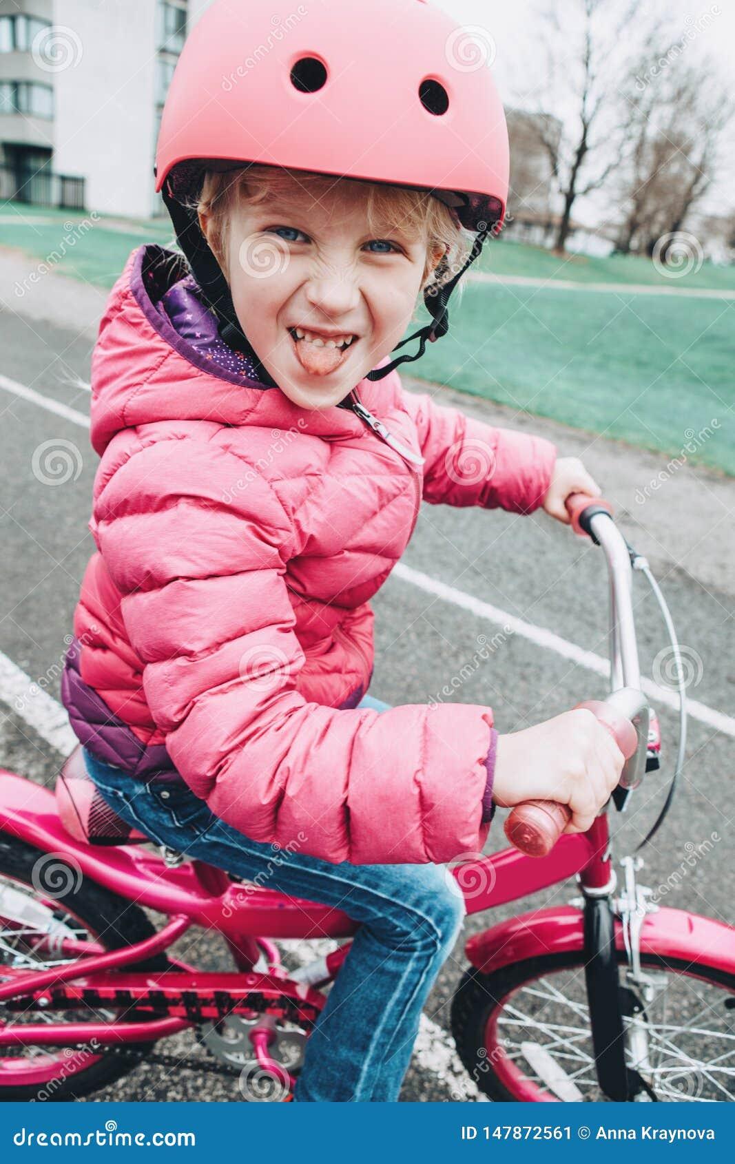 Bicyclette de v?lo de rose d ?quitation de fille d ?l?ve du cours pr?paratoire dans le casque sur la route d arri?re-cour dehors