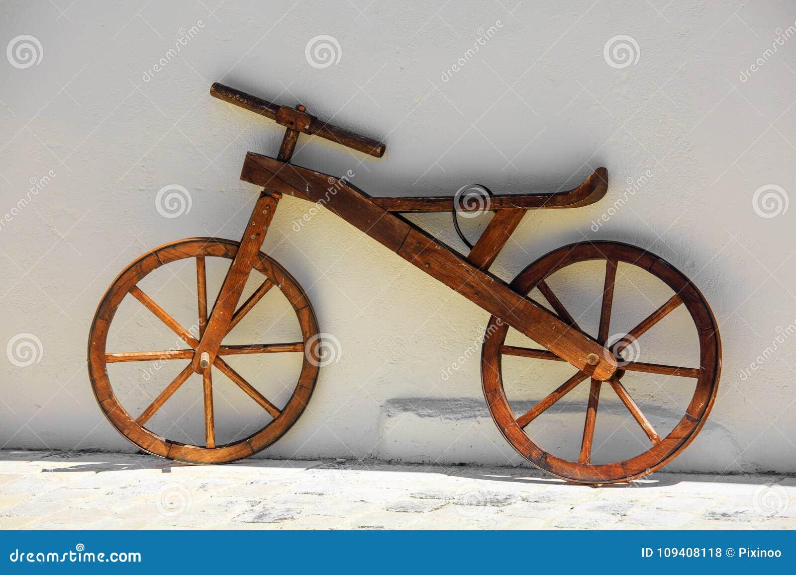 Bicyclette en bois de vintage contre le mur blanc