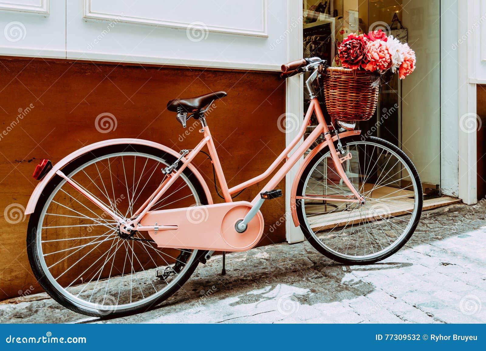 bicyclette rose de vintage avec un panier d coratif de se garer de fleurs photo stock image du. Black Bedroom Furniture Sets. Home Design Ideas
