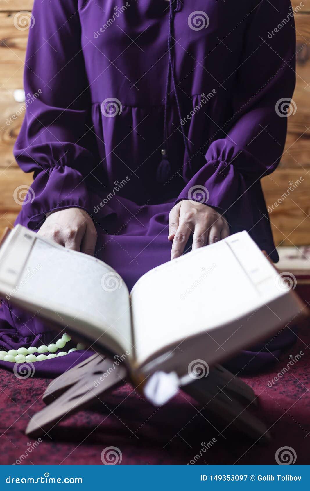 Biddende jonge moslimvrouw Meisje dat van het Middenoosten en heilige Quran bidt het leest Moslimvrouw die Quran bestuderen