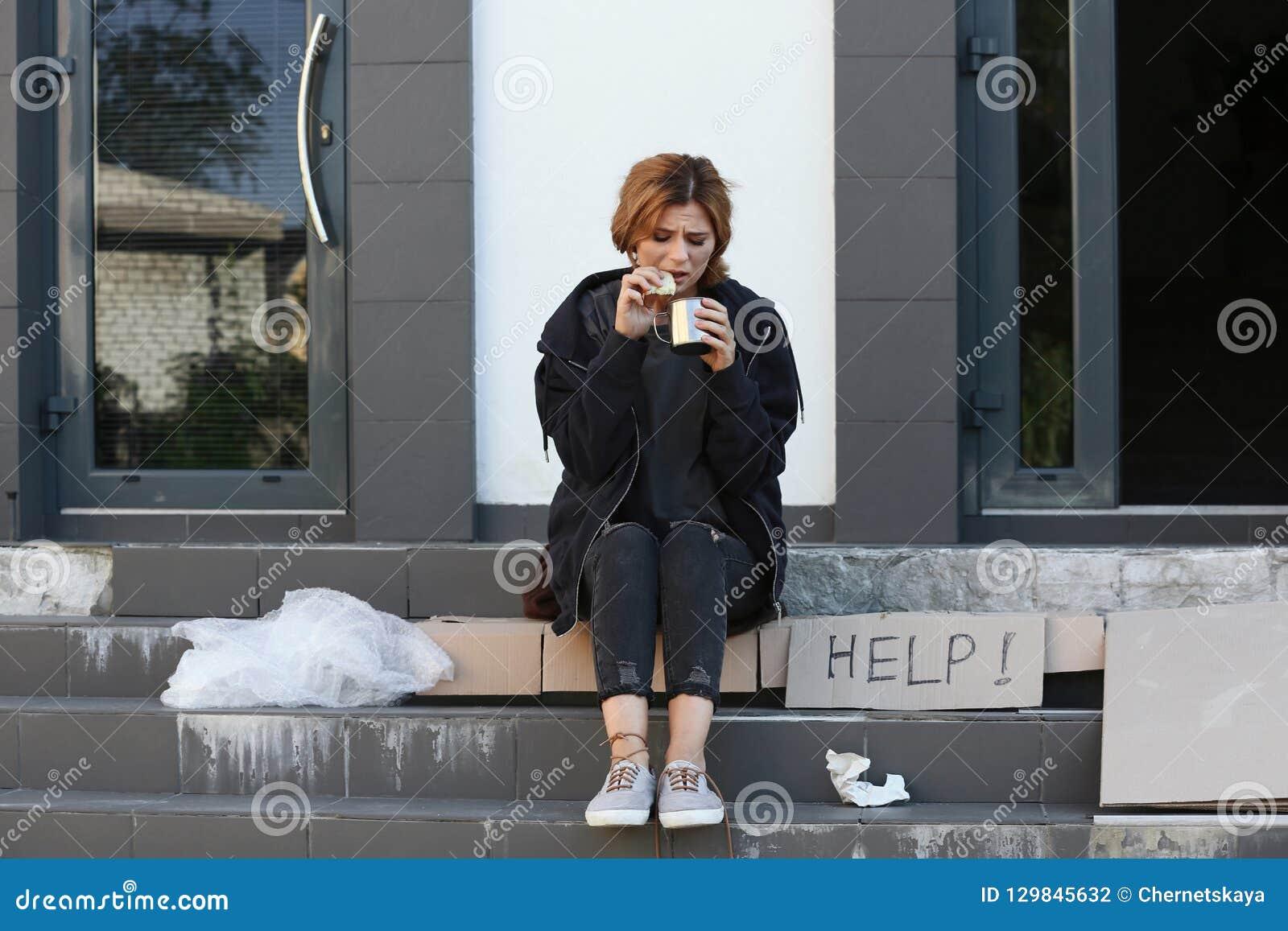 Biedna kobieta z kawałkiem chleb i kubek
