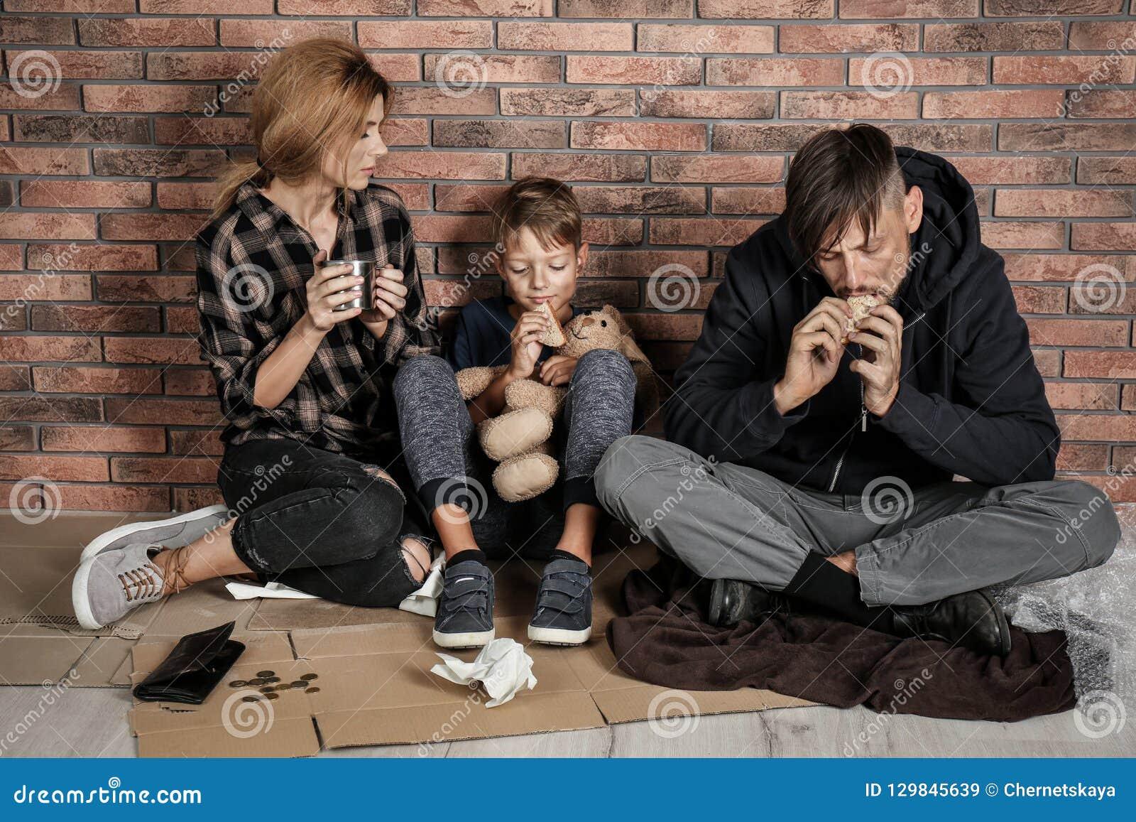 Biedny bezdomny rodzinny obsiadanie na podłodze