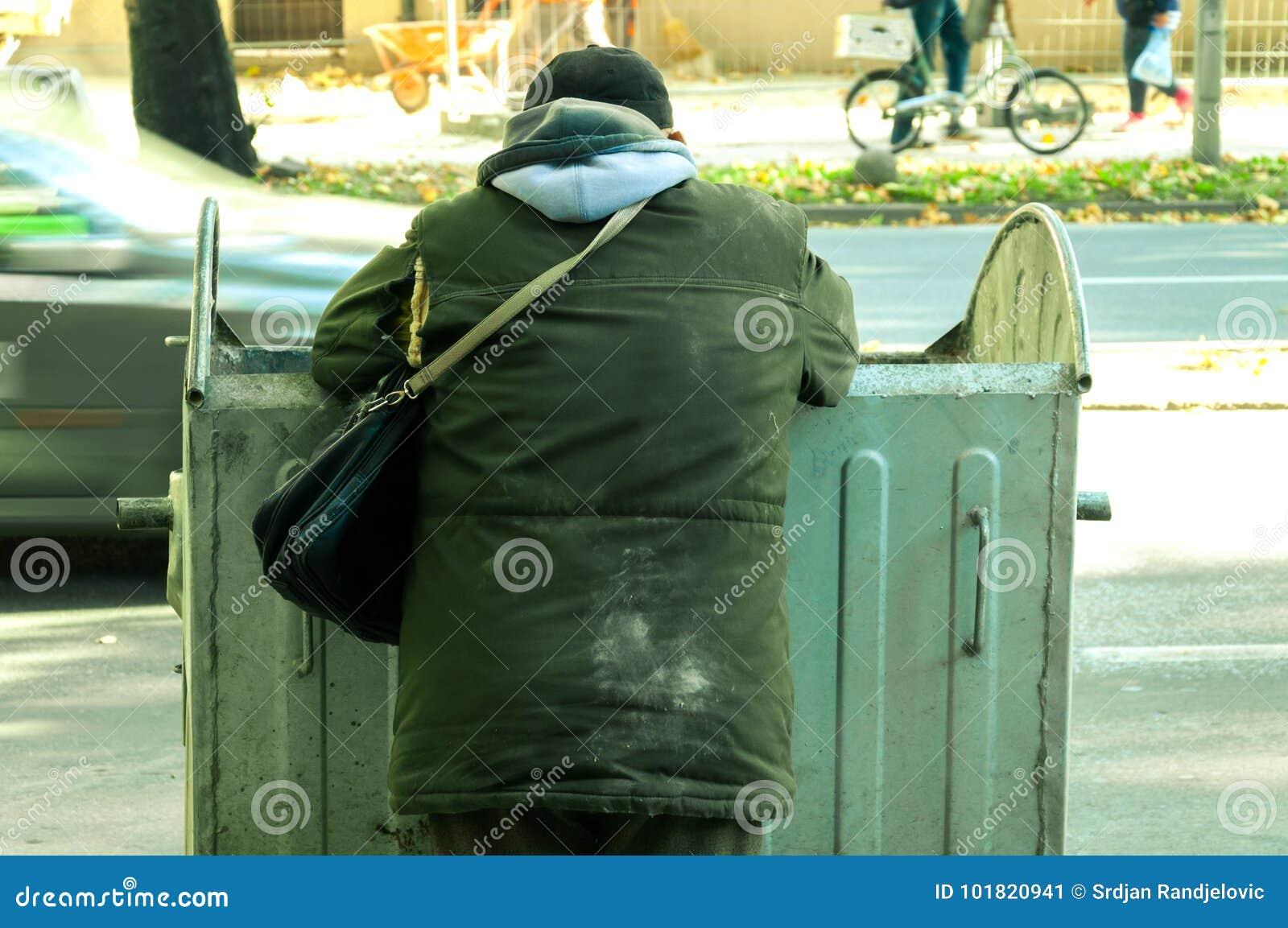 Biedny i głodny bezdomny mężczyzna patrzeje dla jedzenia w śmietniku na miastowej ulicie w mieście w brudnych ubraniach