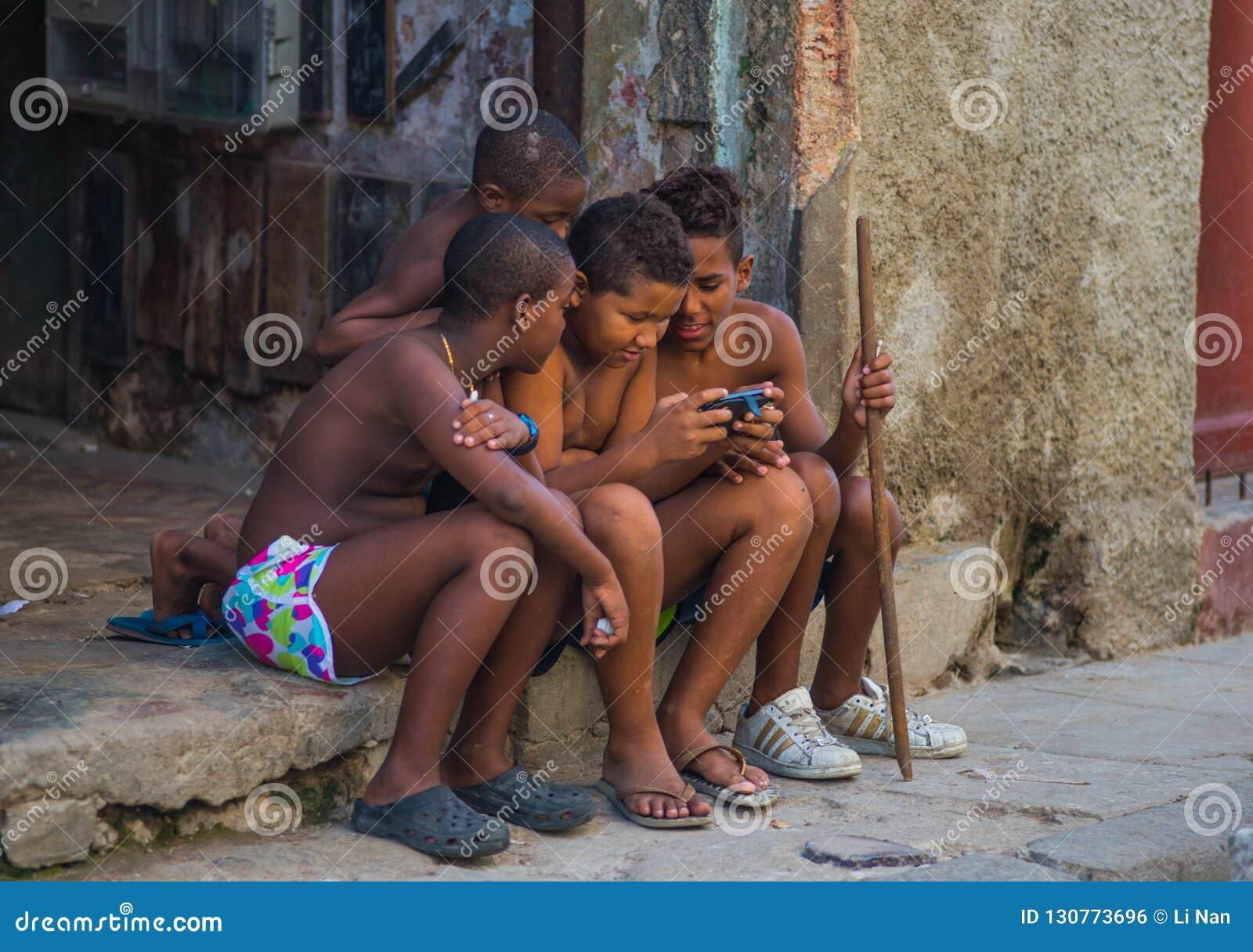 Biedny Kubański chłopiec zdobycza portret w tradycyjnej kolonialnej alei z starym życie stylem w stary Hawańskim, Kuba, Ameryka