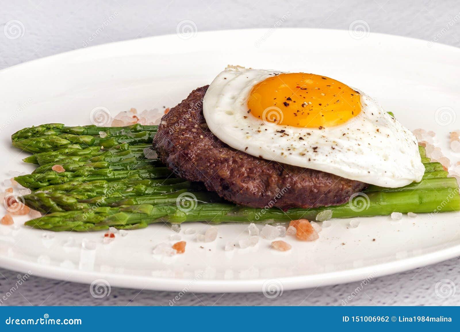 Biefstuk van fijngehakt rundvlees met gebraden eieren en verse groene asperge