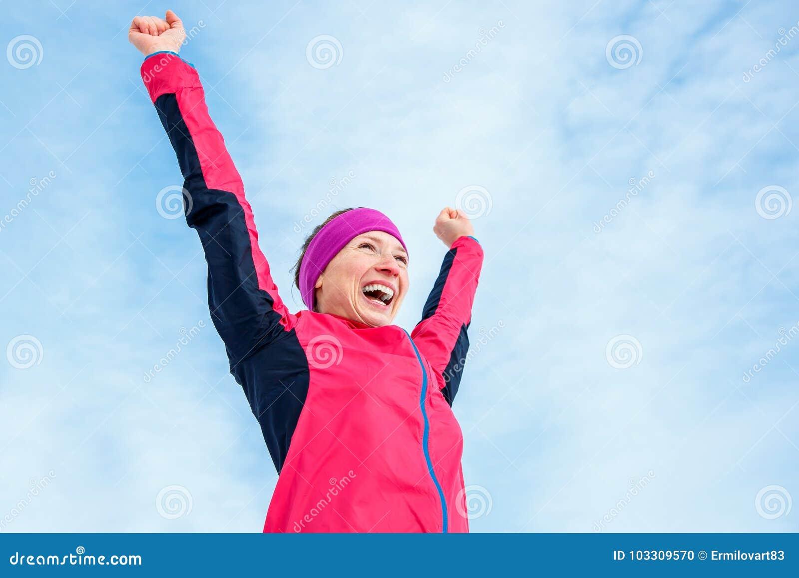 Biegać i sporta sukces Szczęśliwy kobiety odświętności zwycięstwo i podwyżki jego wręcza up Żeński biegacz pomyślny przeciw niebi