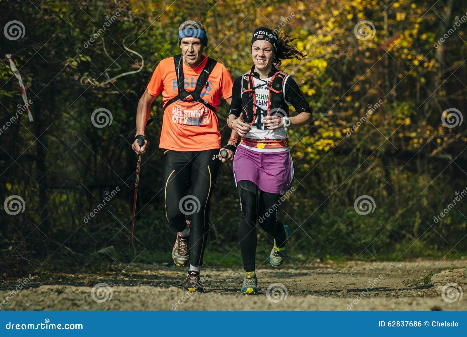 Biegać wzdłuż młodej kobiety w jesień lesie i starego człowieka