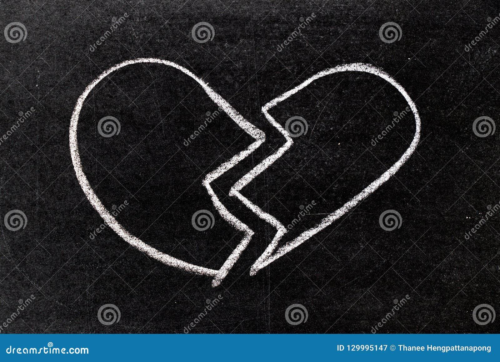 Biel kredy ręki rysunek w złamane serce kształcie na blackboard