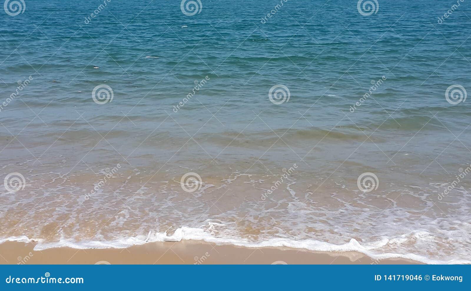 Biel piana na seashore, błękitna ocean woda i małe fale na plaży, Być na wakacjach i podróżujemy temat - Lagos, Nigeria -