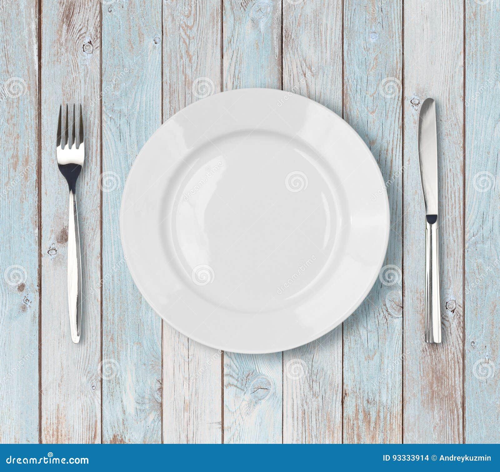 Bielu obiadowego talerza pusty położenie na błękitnym drewnianym stole