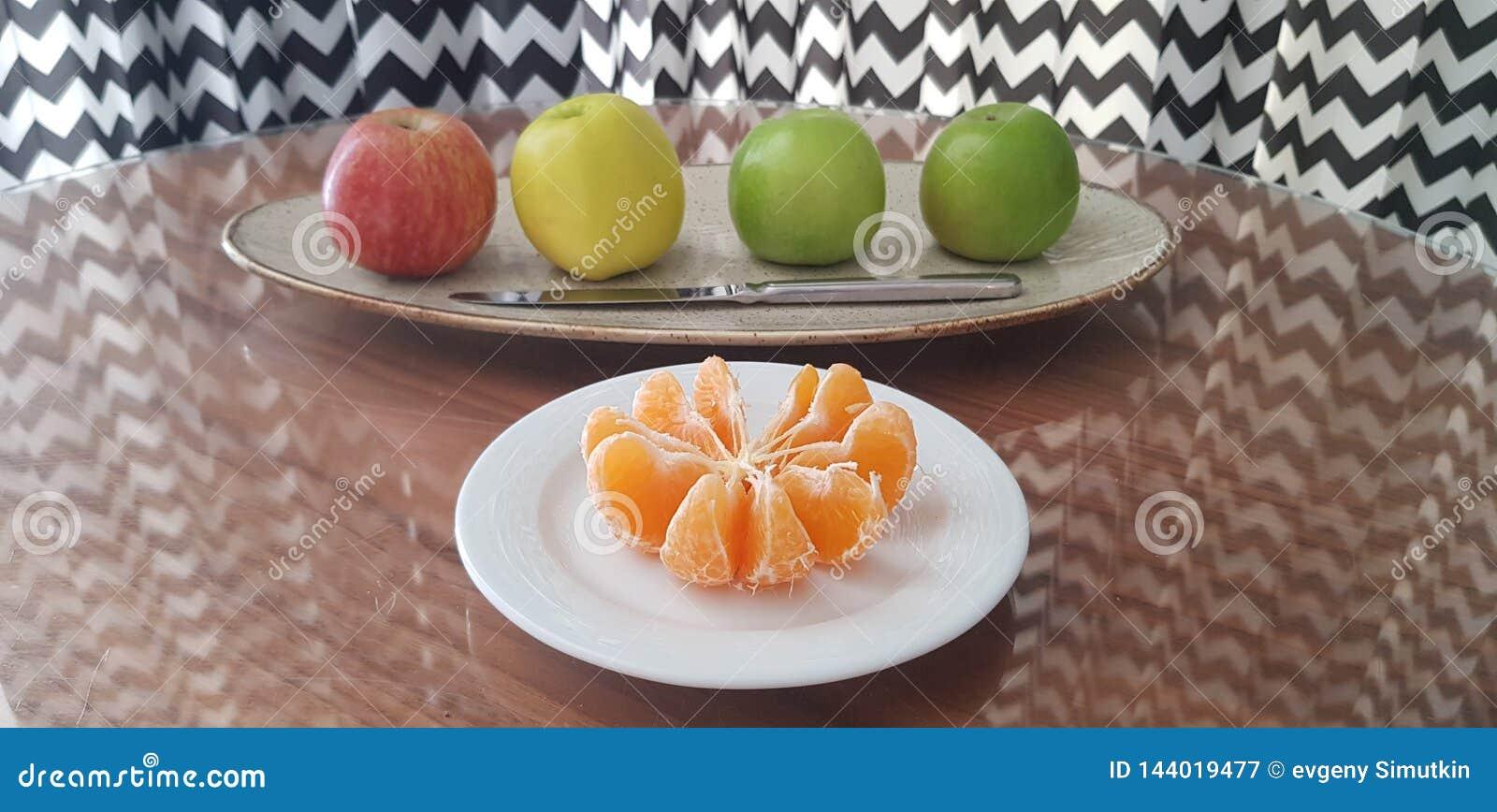 Bielu talerz z obranymi mandarynka plasterkami i naczynie z cztery jabłkami różnorodni kolory i nóż