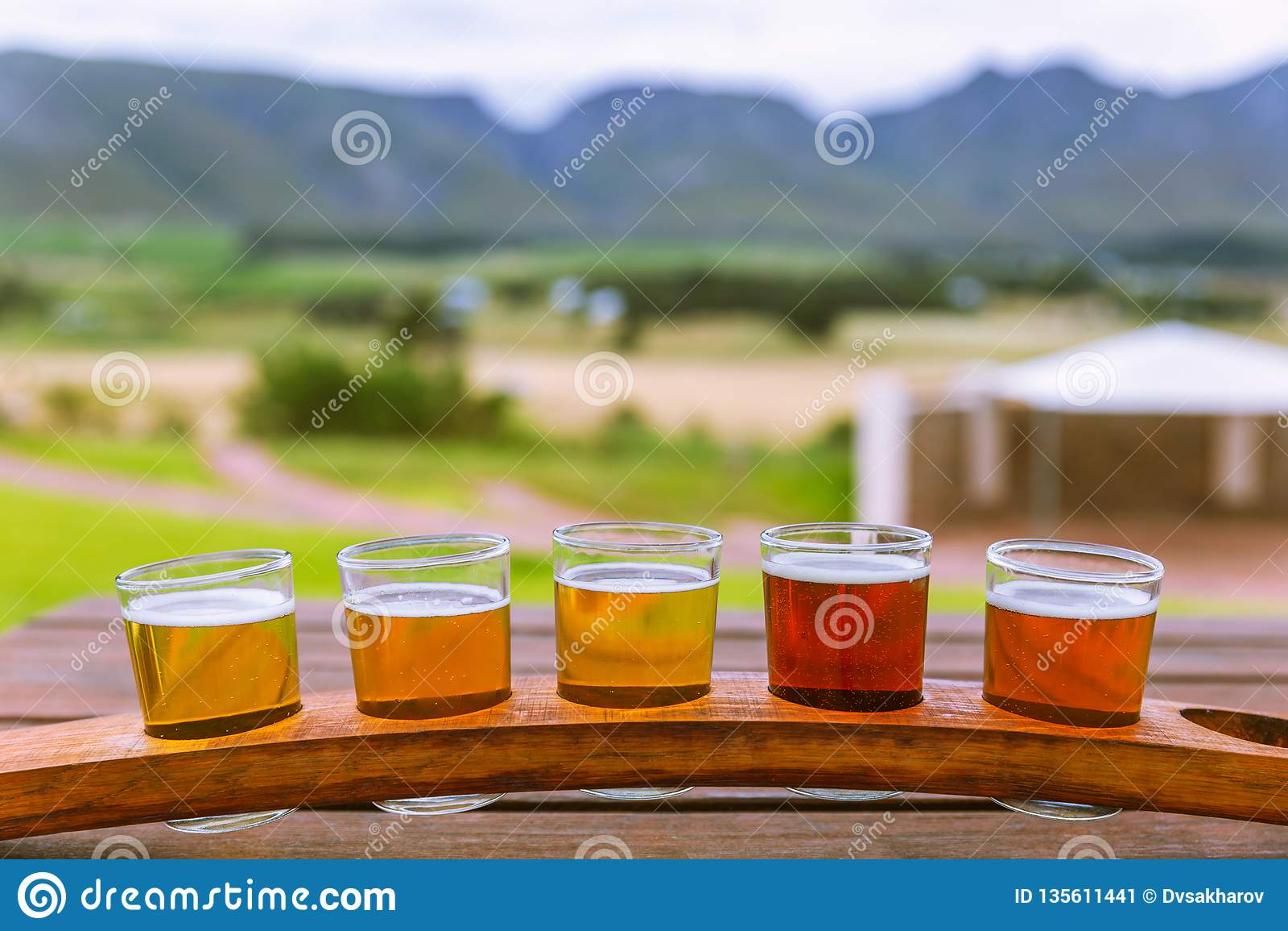 Bier, das Gläser auf einem hölzernen Behälter außerhalb der Brauerei schmeckt
