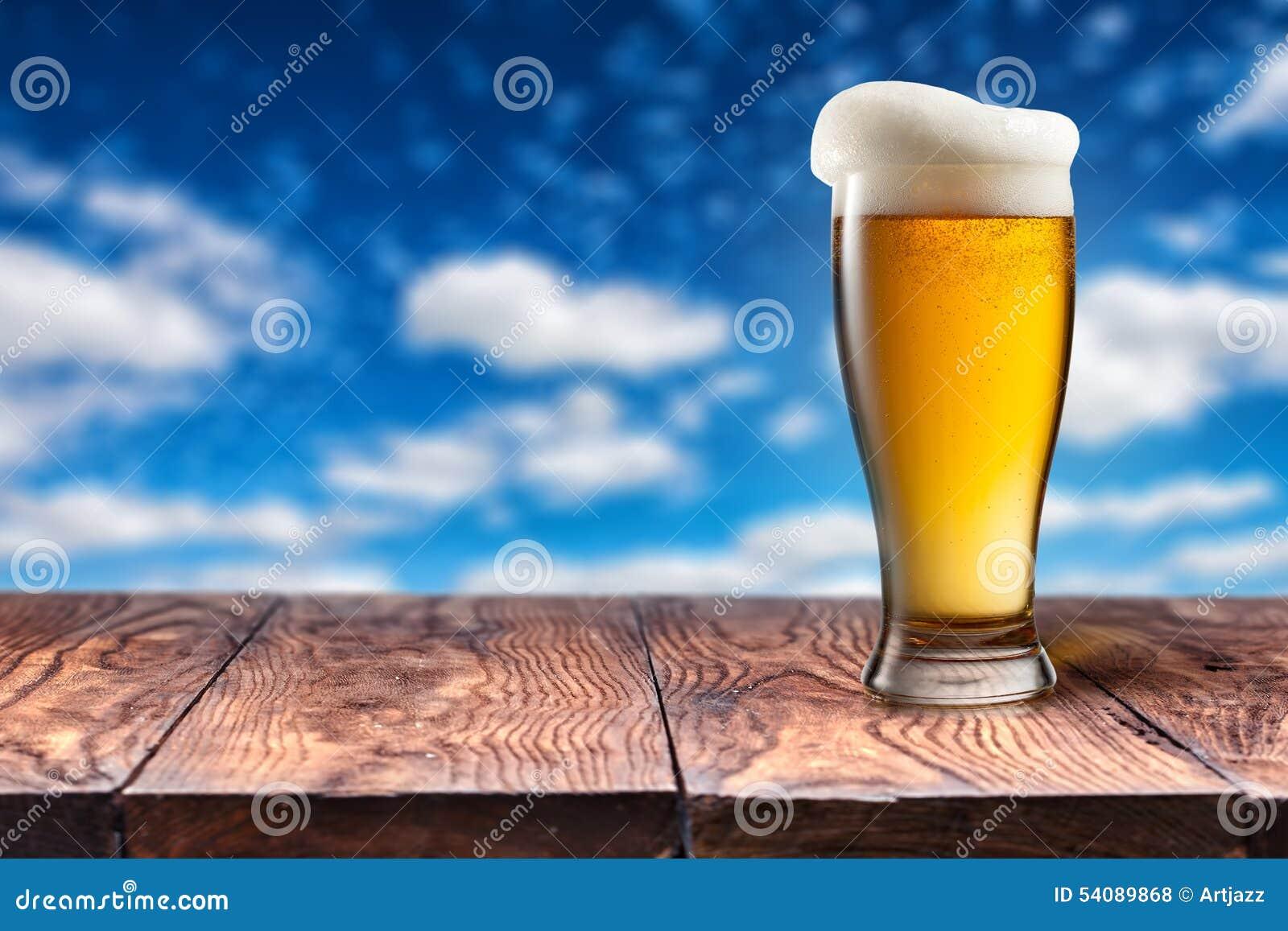 Bier in glas op houten lijst tegen blauwe hemel