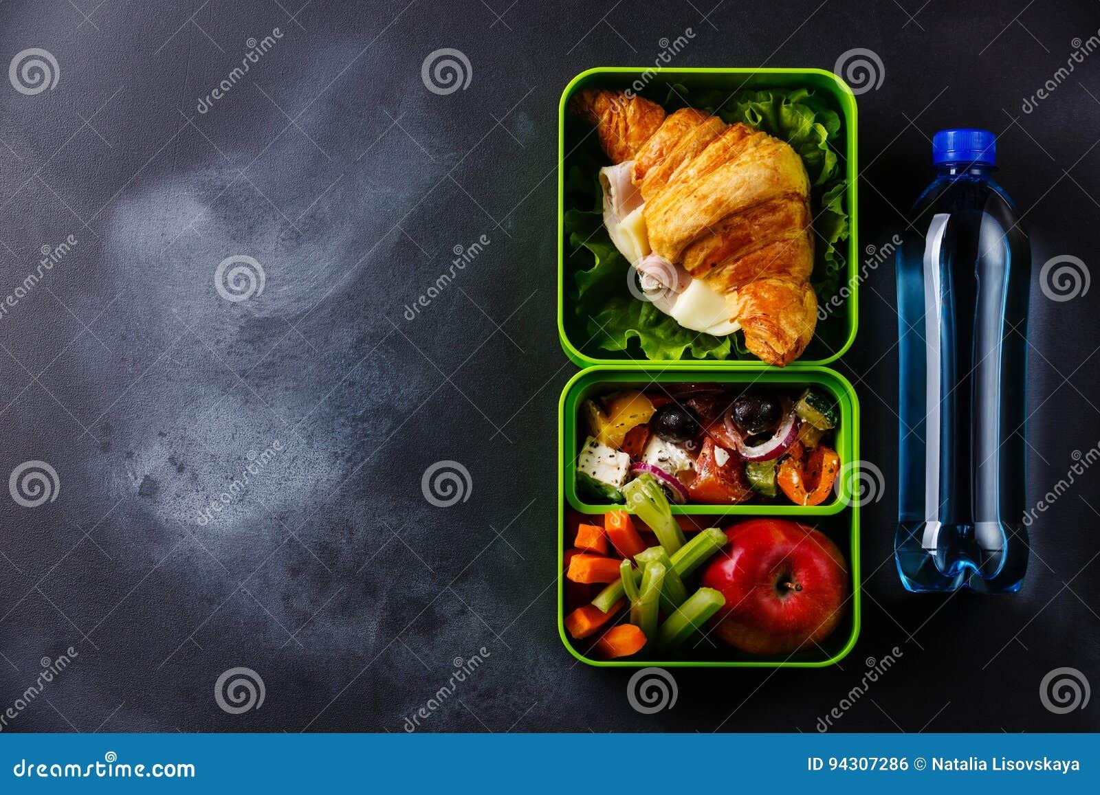 Bierze out karmowego lunchu pudełko z Croissant, Grecką sałatką i wodą,