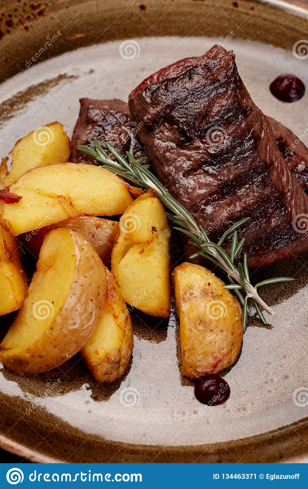 Bife da carne e alecrins grelhados das batatas na placa