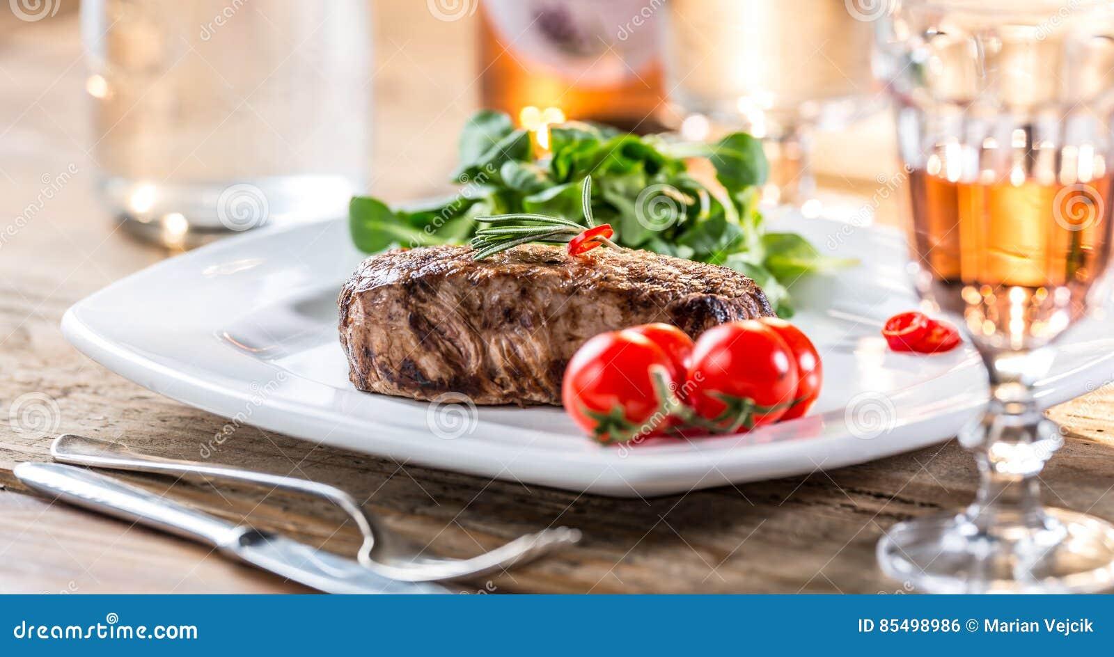 Bife de carne Bife de carne suculento Bife gourmet com vegetais e vidro do vinho cor-de-rosa na tabela de madeira