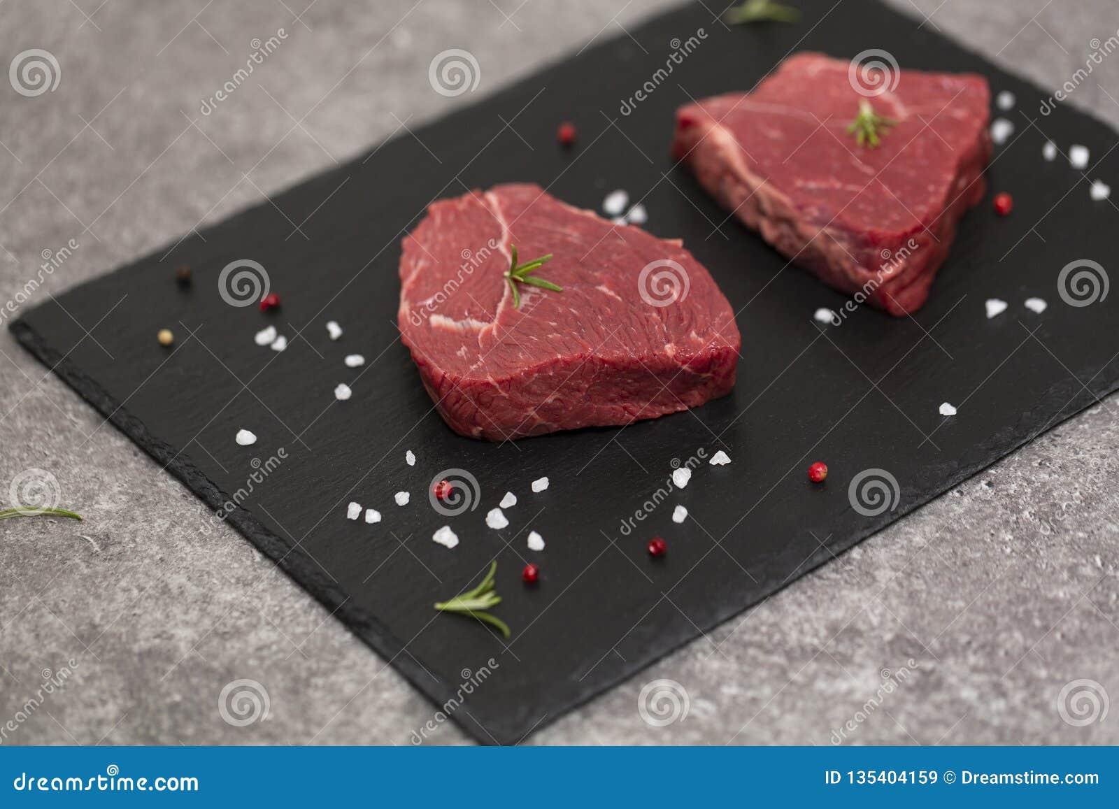Bife e especiarias crus na placa da ardósia Carne crua no fundo preto
