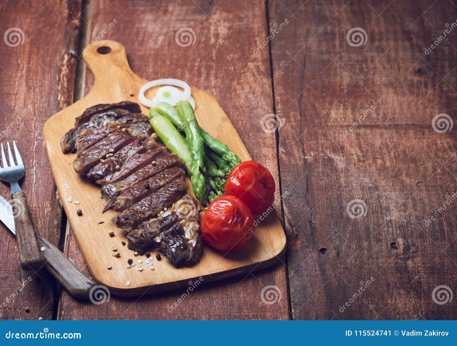 Bife grelhado com asparaguas e tomates em um fundo rústico de madeira