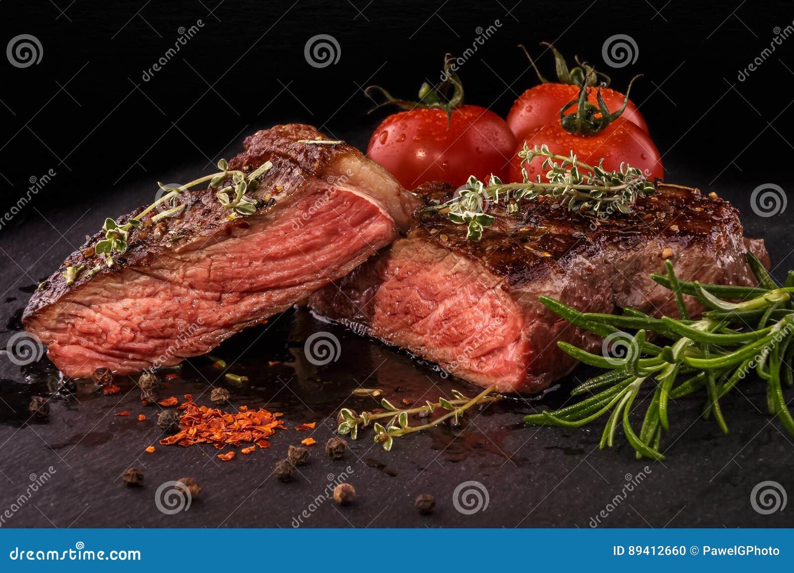 Bife grelhado cortado com as especiarias na laje da ardósia