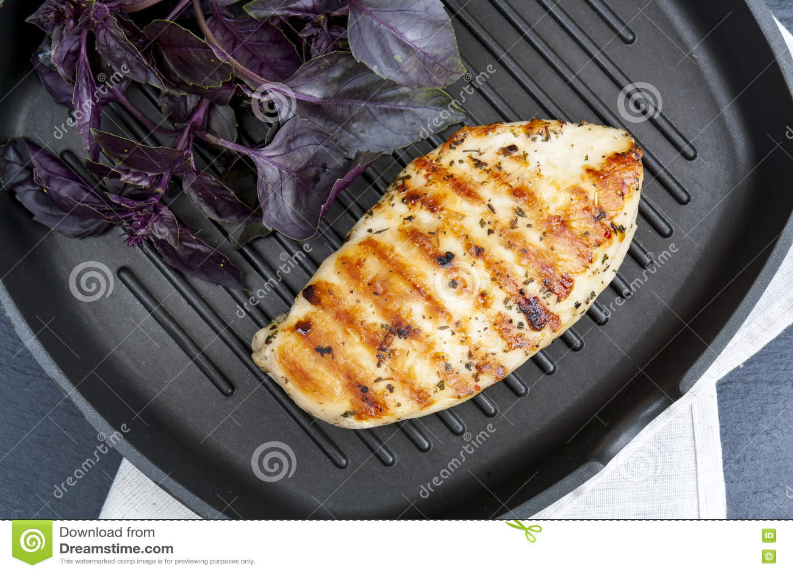 Bife grelhado do peito de frango com manjericão violeta no gri da bandeja do Teflon