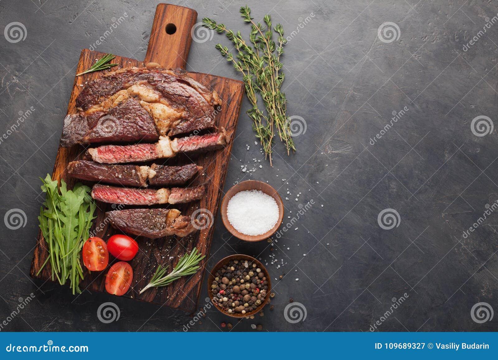 Bife grelhado do ribeye com vinho tinto, ervas e especiarias em um fundo de pedra escuro Vista superior com espaço da cópia para