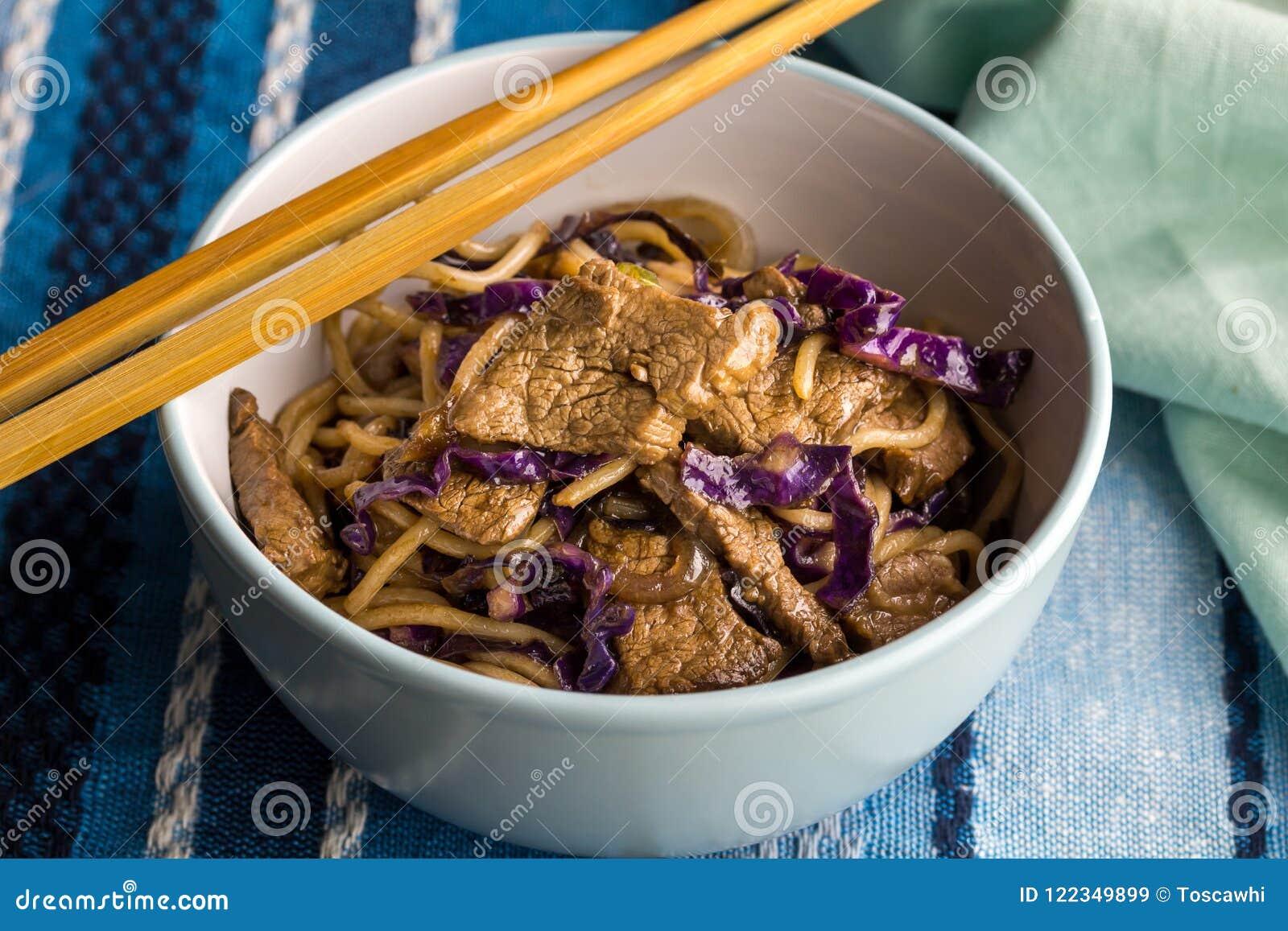 Bife, macarronetes e close up roxo da couve na bacia com hashi