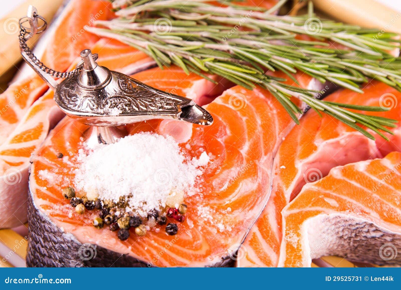 Bife salmon cru com rosemary em uma placa de bambu
