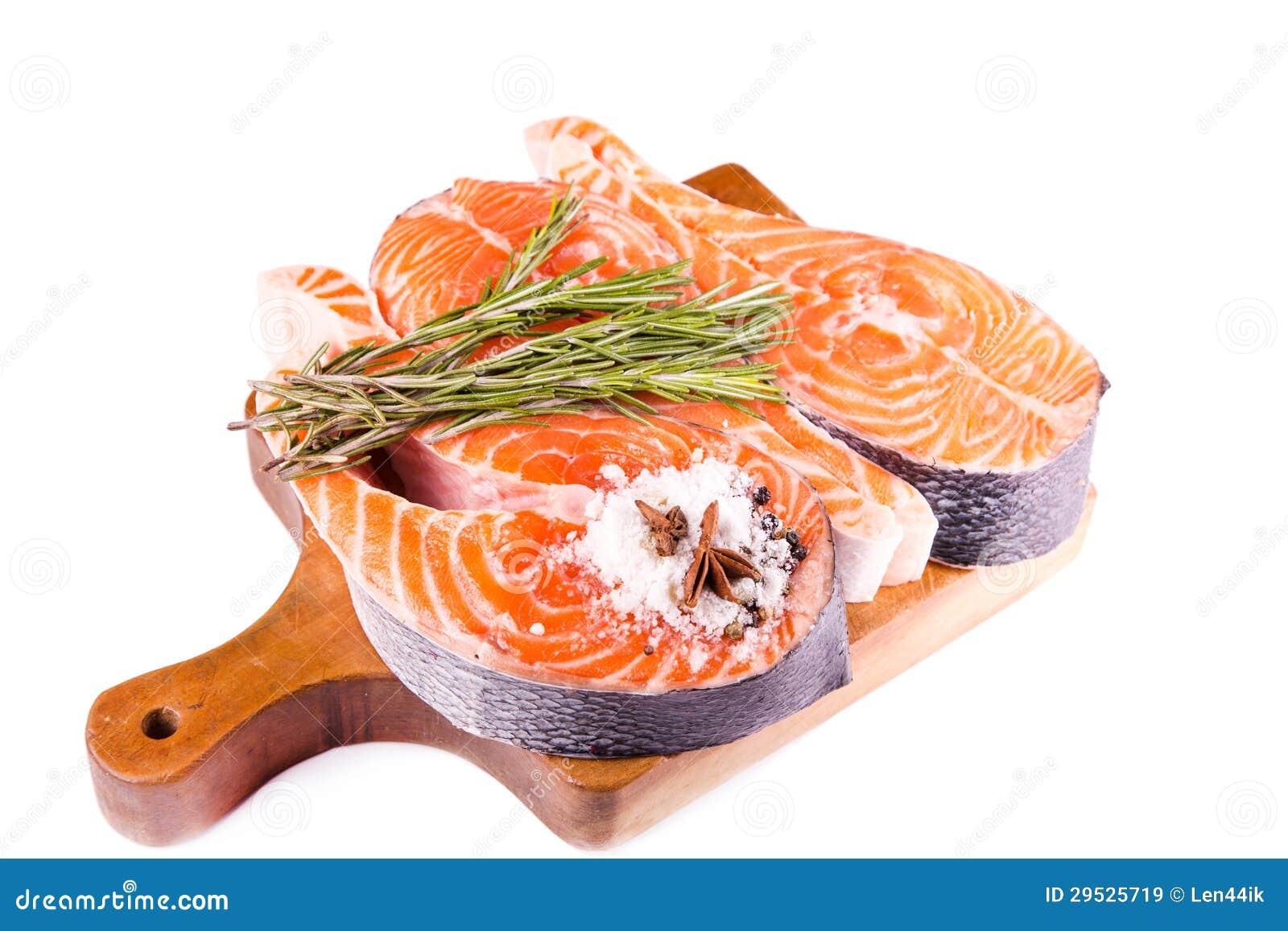 Bife salmon cru com rosemary em uma placa de madeira