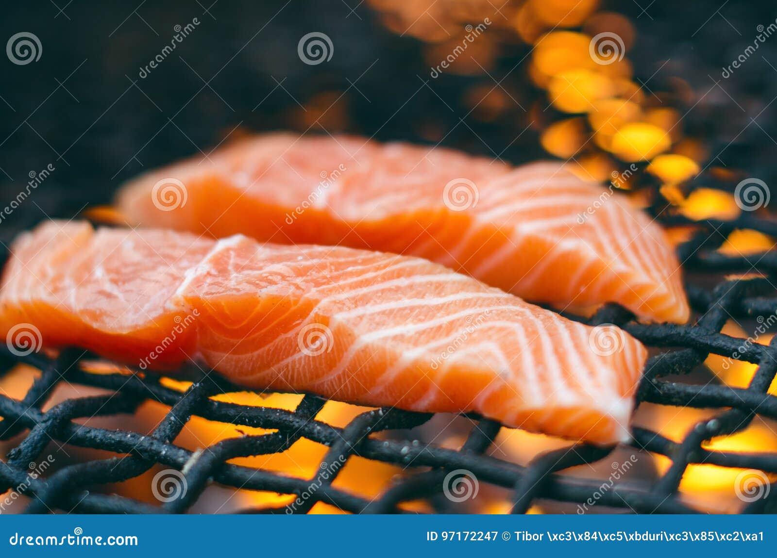Bifes salmon grelhados em uma grade Grade da chama do fogo Cozinha do restaurante e do jardim Partido de jardim Prato saudável