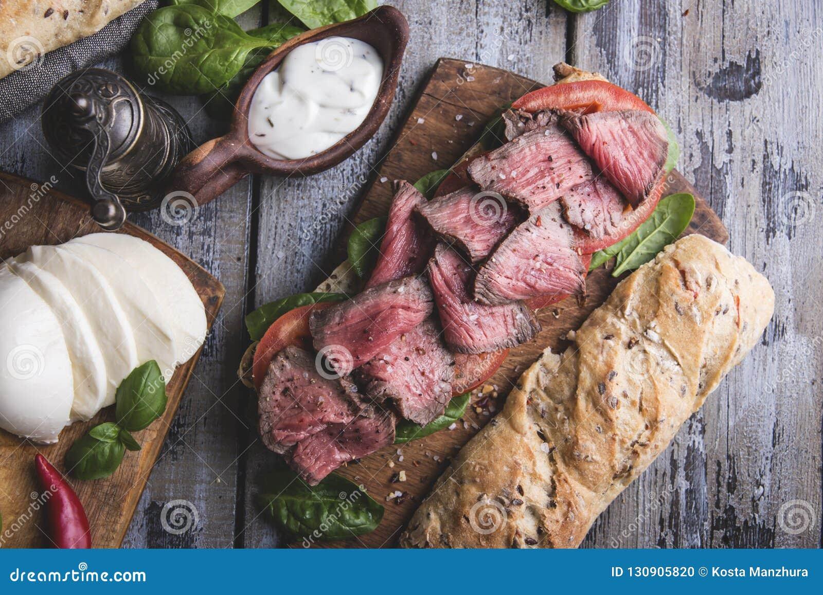 Biffsmörgås, skivat steknötkött, ost, spenatsidor, tomat